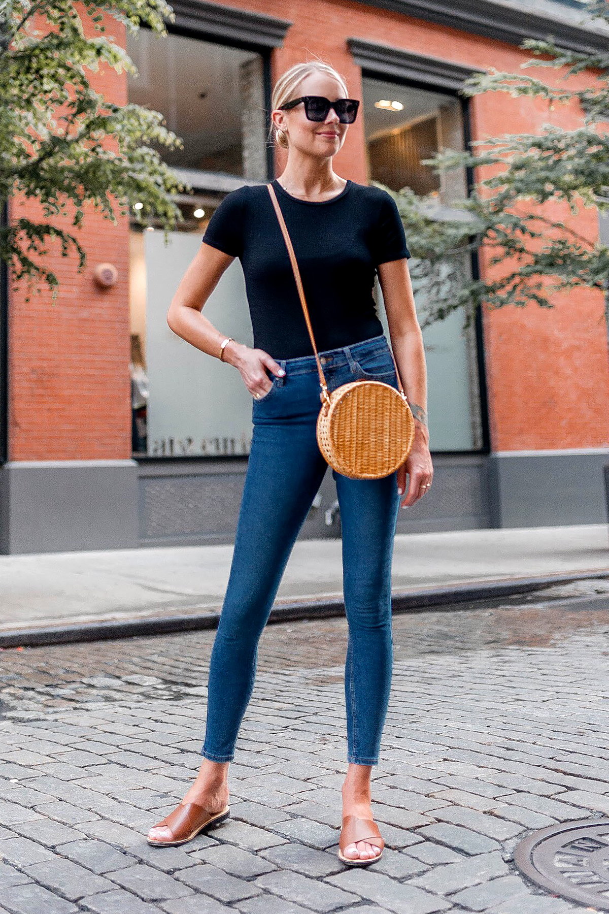 Blonde Woman Wearing Bloomingdales Black Short Sleeve Bodysuit Denim Skinny Jeans Tan Flat Sandals Circle Straw Handbag Black Sunglasses Fashion Jackson Dallas Blogger Fashion Blogger New York Street Style