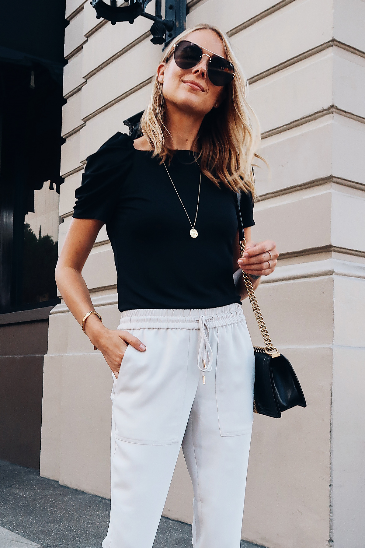 Blonde Woman Wearing Ann Taylor Black Ruched Sleeve Top Ivory Jogger Pants Aviator Sunglasses Long Gold Disc Necklace Fashion Jackson San Diego Blogger Fashion Blogger Street Style