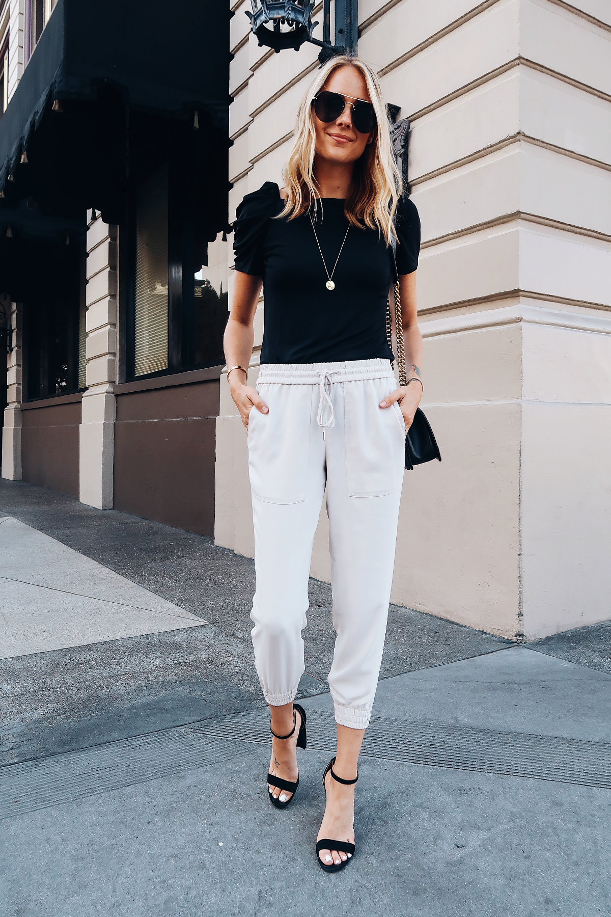 Blonde Woman Wearing Ann Taylor Black Ruched Sleeve Top Ivory Jogger Pants Black Ankle Strap Heeled Sandals Aviator Sunglasses Long Gold Disc Necklace Fashion Jackson San Diego Blogger Fashion Blogger Street Style