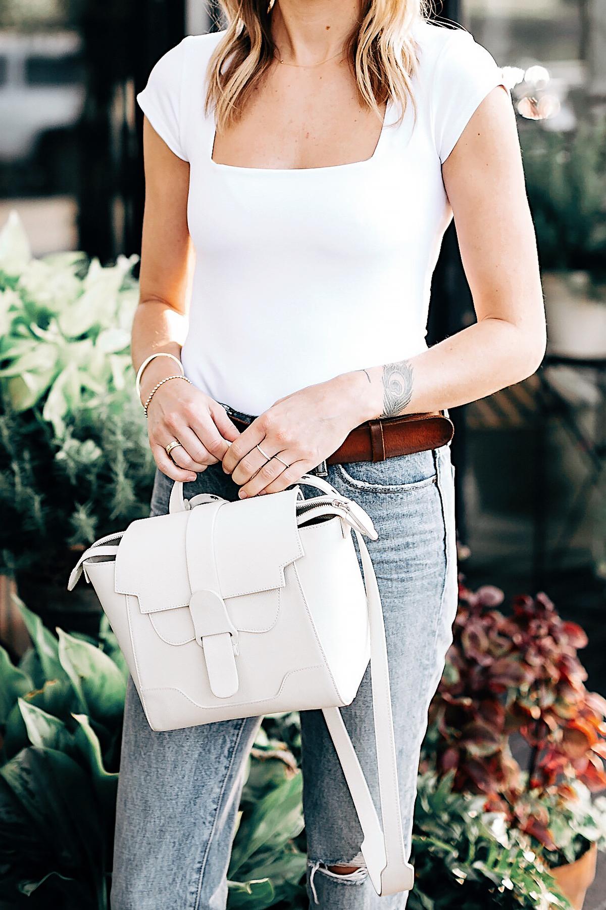 Blonde Woman Wearing Senreve Mini Maestra Cream Free People White Bodysuit Ripped Jeans Fashion Jackson San Diego Fashion Blogger Street Style