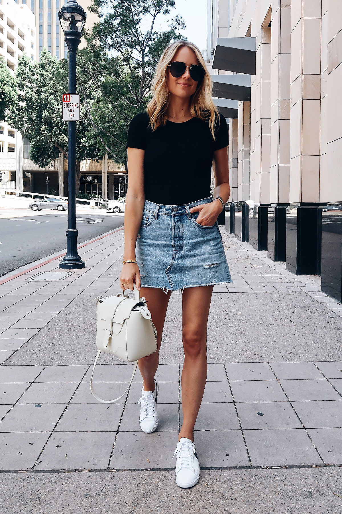 054938fcf71 Blonde Woman Wearing Short Sleeve Black Bodysuit Levis Denim Skirt Nike  White Sneakers Senreve White Mini