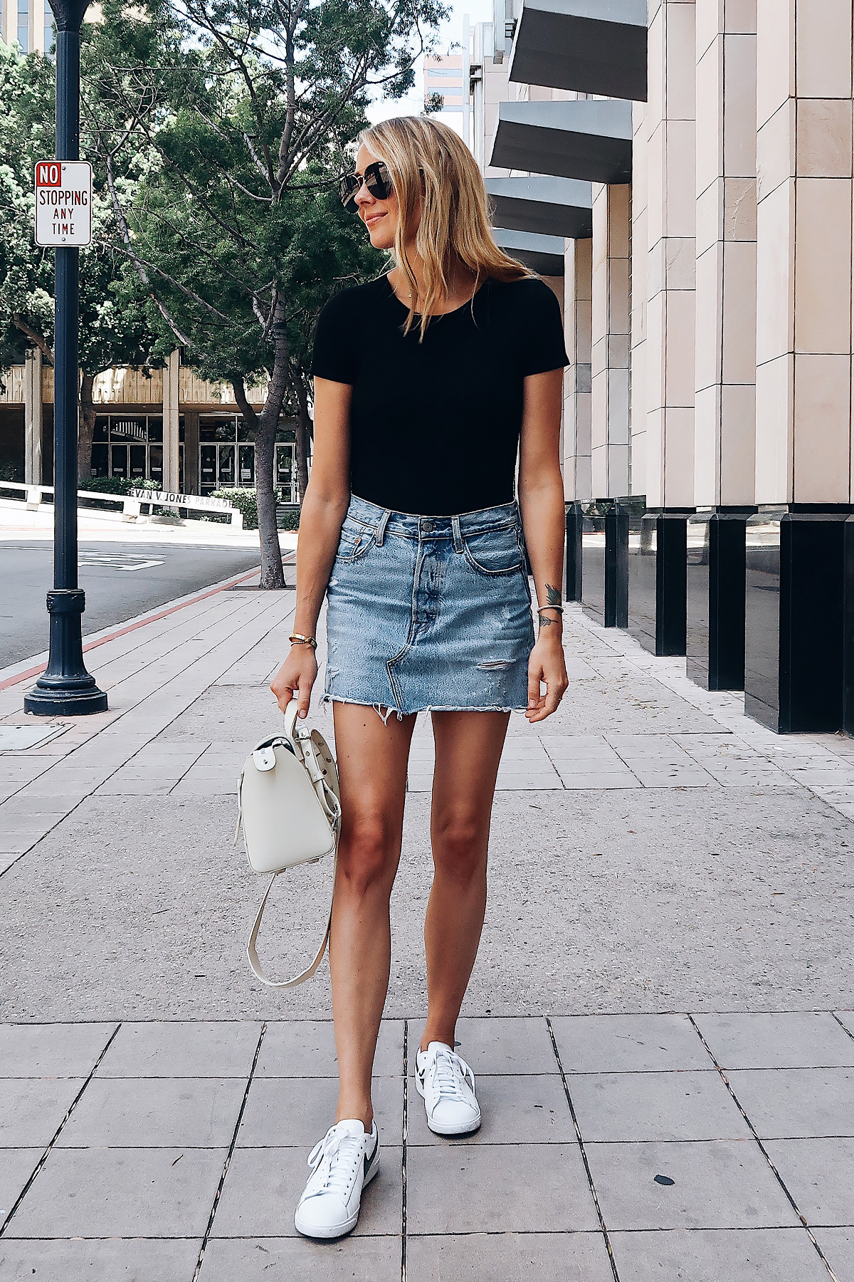 Blonde Woman Wearing Fashion Jackson Short Sleeve Black Bodysuit Levis Denim Skirt Nike White Sneakers Senreve White Mini Maestra Handbag Aviator Sunglasses Fashion Jackson San Diego Fashion Blogger Street Style