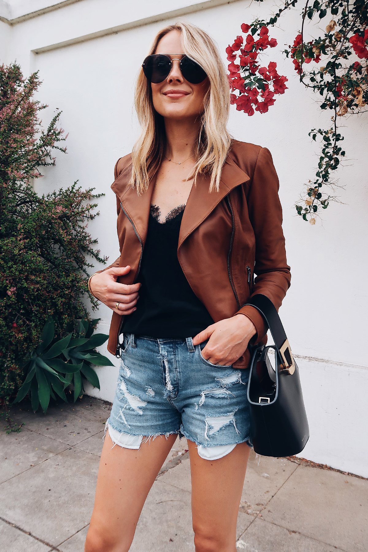 Blonde Woman Wearing Fashion Jackson Tan Leather Jacket Black Lace Cami Denim Ripped Shorts Aviator Sunglasses Danse Lente Black Handbag Fashion Jackson San Diego Fashion Blogger Street Style