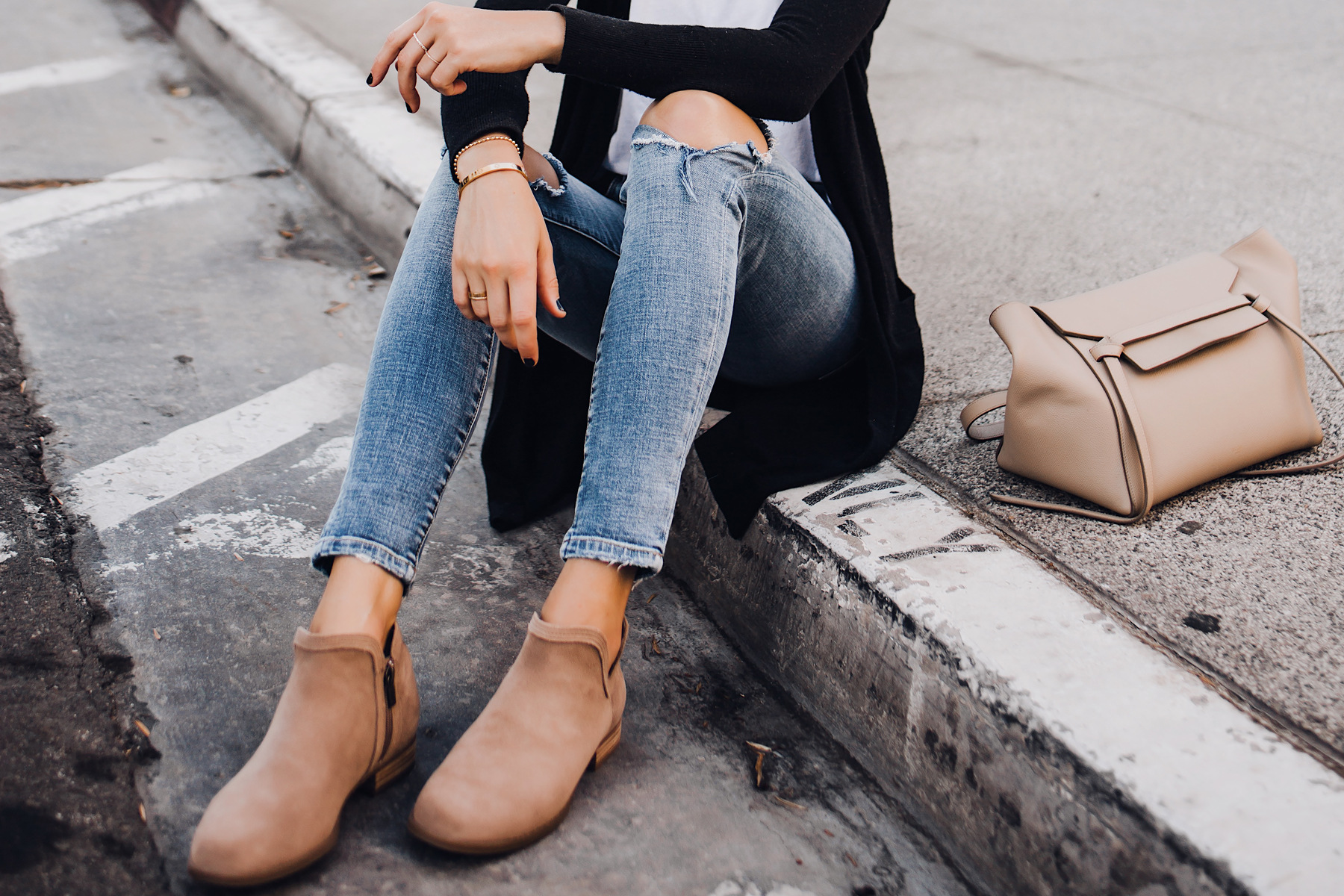 Woman Wearing Black Cardigan White Tshirt Ripped Skinny Jeans Celine Mini Belt Bag Uggs Koolaburra Tan Booties Fashion Jackson San Diego Fashion Blogger Street Style