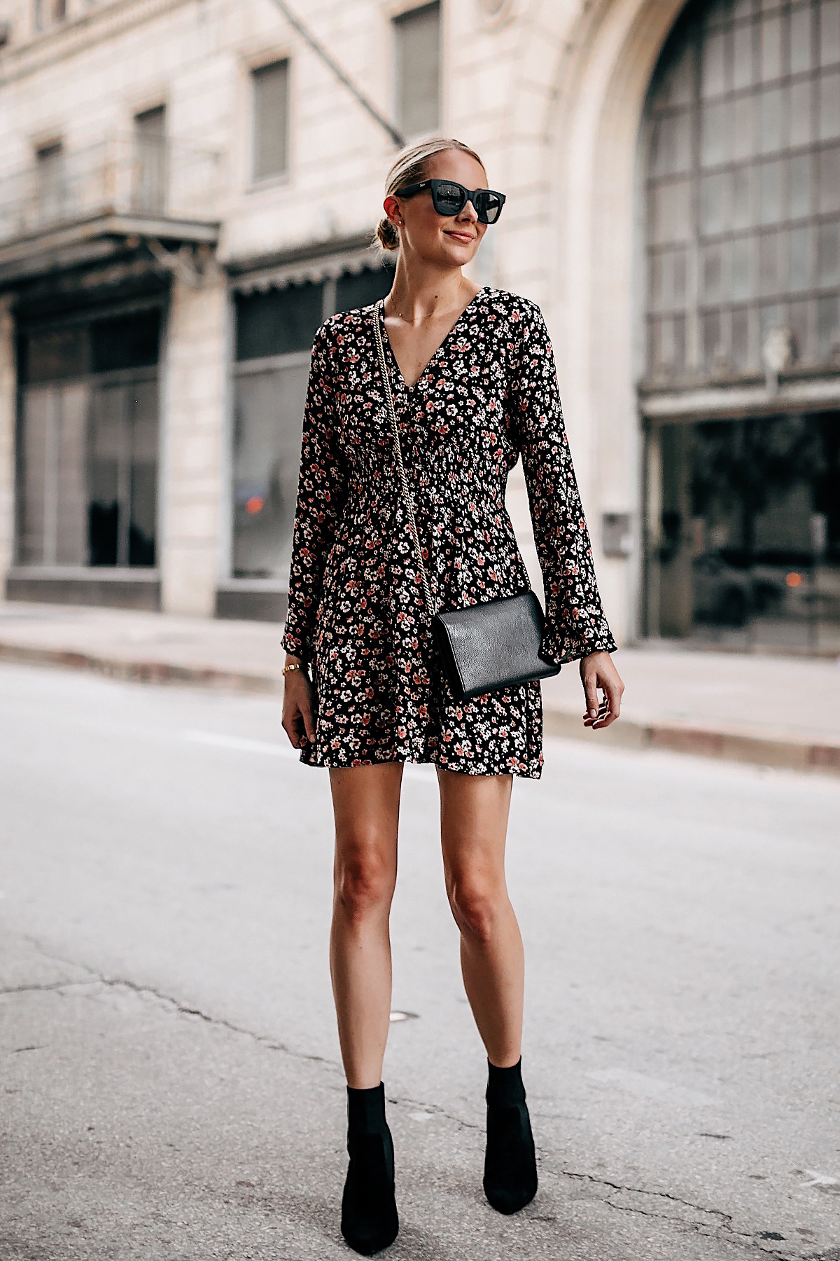 Blonde Woman Wearing Black Floral Long Sleeve Mini Dress Black Heeled Ankle Booties Gold Chain Black Crossbody Handbag Black Sunglasses Fashion Jackson San Diego Fashion Blogger Street Style