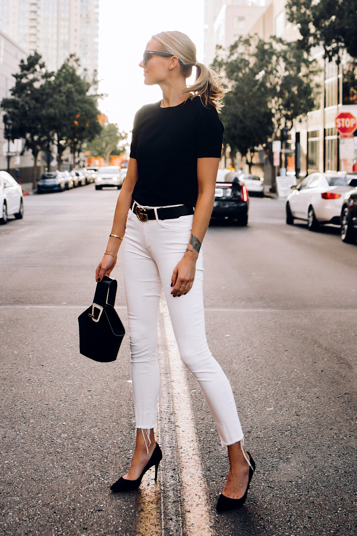 Woman Wearing Black Short Sleeve Sweater Raw Hem White Skinny Jeans Black Pumps Black Gucci Belt Black Bucket Bag Fashion Jackson San Diego Fashion Blogger Street Style