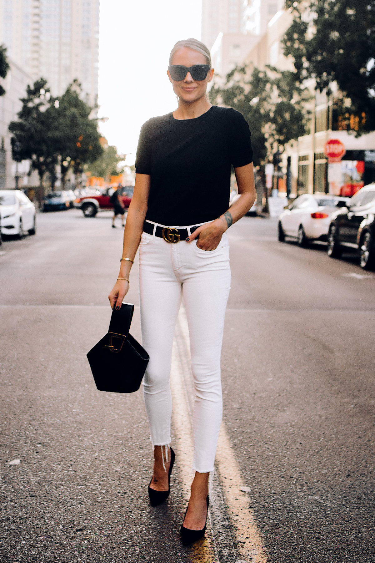 Blonde Woman Wearing Black Short Sleeve Sweater Raw Hem White Skinny Jeans Black Pumps Black Gucci Belt Black Bucket Bag Fashion Jackson San Diego Fashion Blogger Street Style