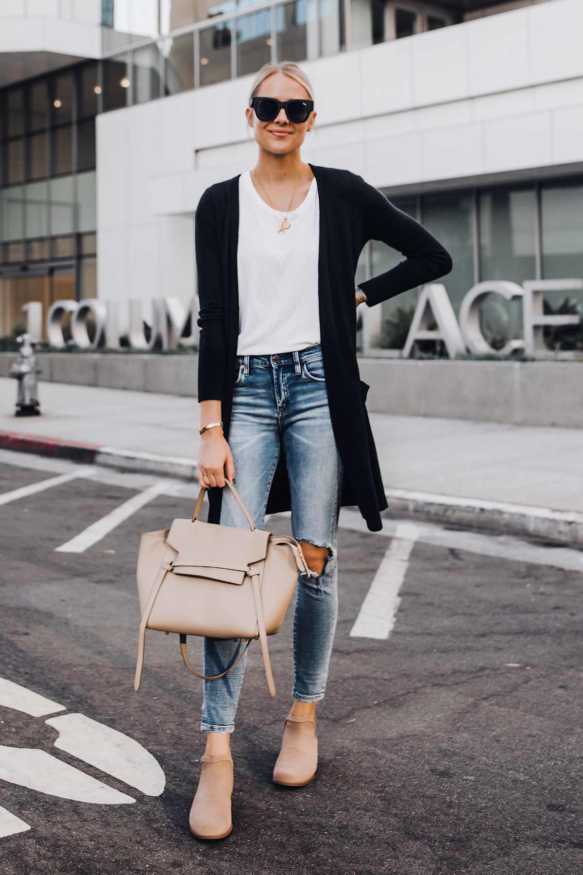 Blonde Woman Wearing Long Black Cardigan White Tshirt Ripped Skinny Jeans Celine Mini Belt Bag Uggs Koolaburra Tan Booties Fashion Jackson San Diego Fashion Blogger Street Style