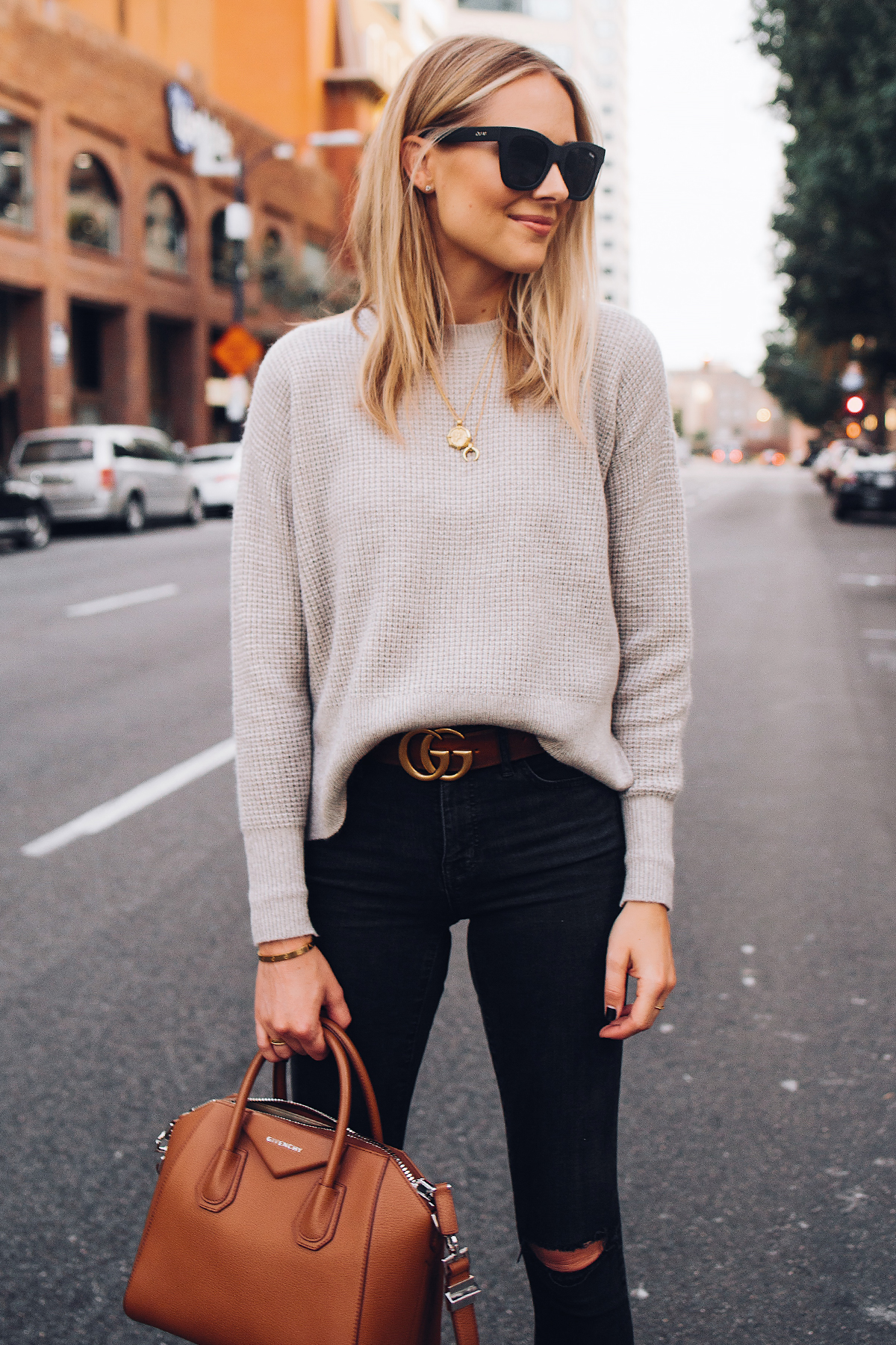 Blonde Woman Wearing Everlane Taupe Cashmere Sweater Black Ripped Skinny Jeans Brown Gucci Logo Belt Black Booties Givenchy Anitogona Cognac Handbag Gold Layered Necklaces Fashion Jackson San Diego Fashion Blogger Street Style