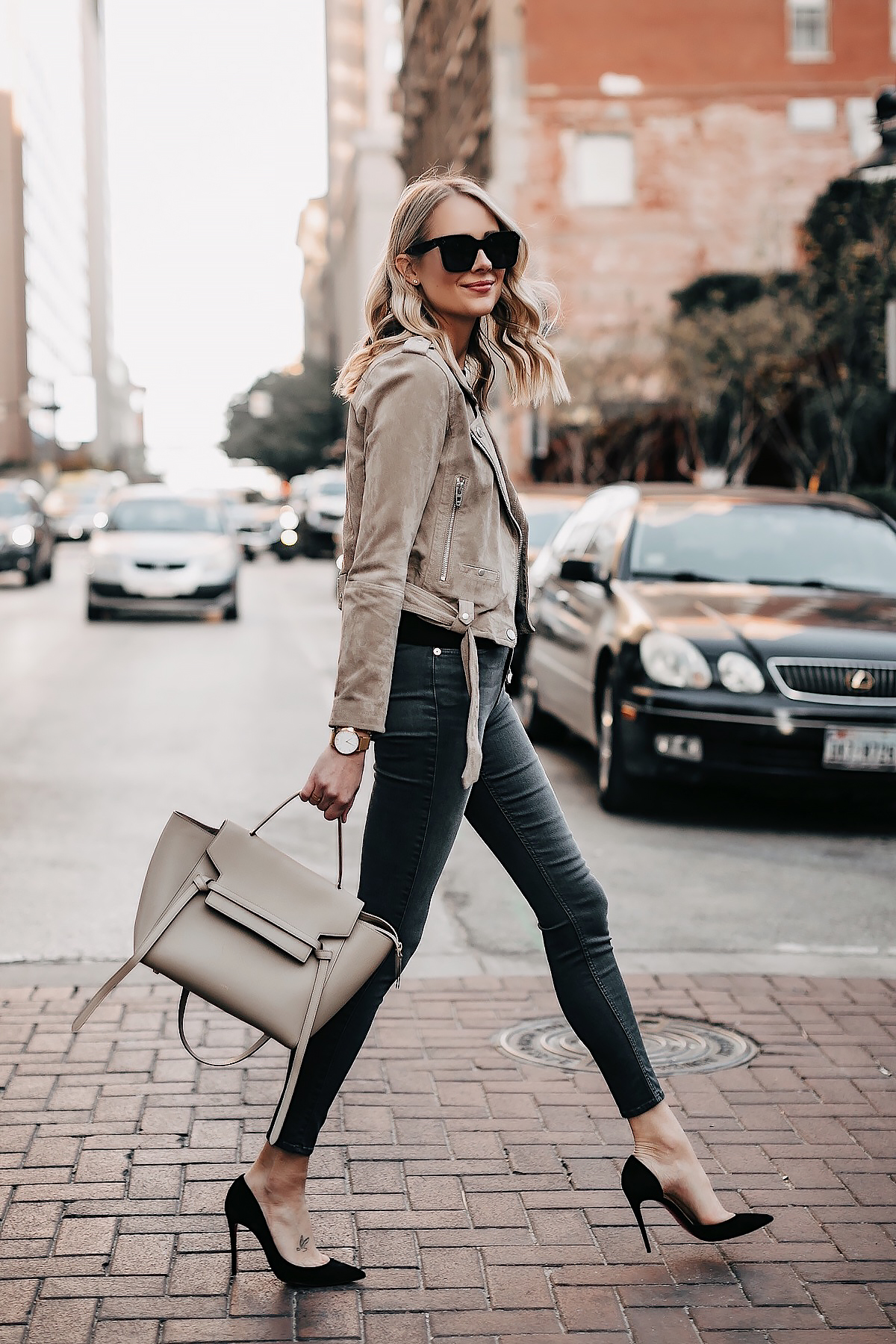 9789e9c9a9 Blonde Woman Wearing Tan Suede Moto Jacket Black Top Grey Skinny Jeans Black  Pumps Celine Mini