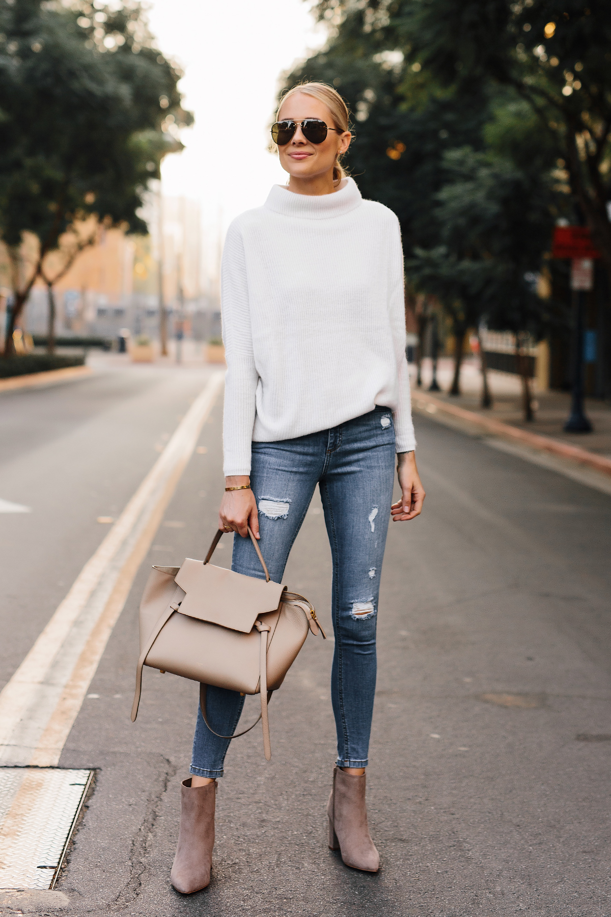 Blonde Woman Wearing White Sweater Denim Ripped Skinny Jeans Steve Madden Taupe Booties Outfit Celine Mini Belt Bag Fashion Jackson San Diego Fashion Blogger Street Style