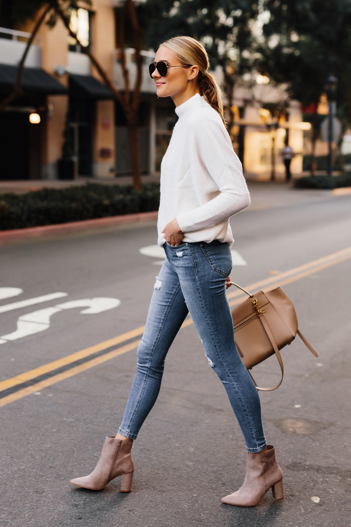 Blonde Woman Wearing White Sweater Denim Ripped Skinny Jeans Steve Madden Taupe Booties Outfit Fashion Jackson San Diego Fashion Blogger Street Style