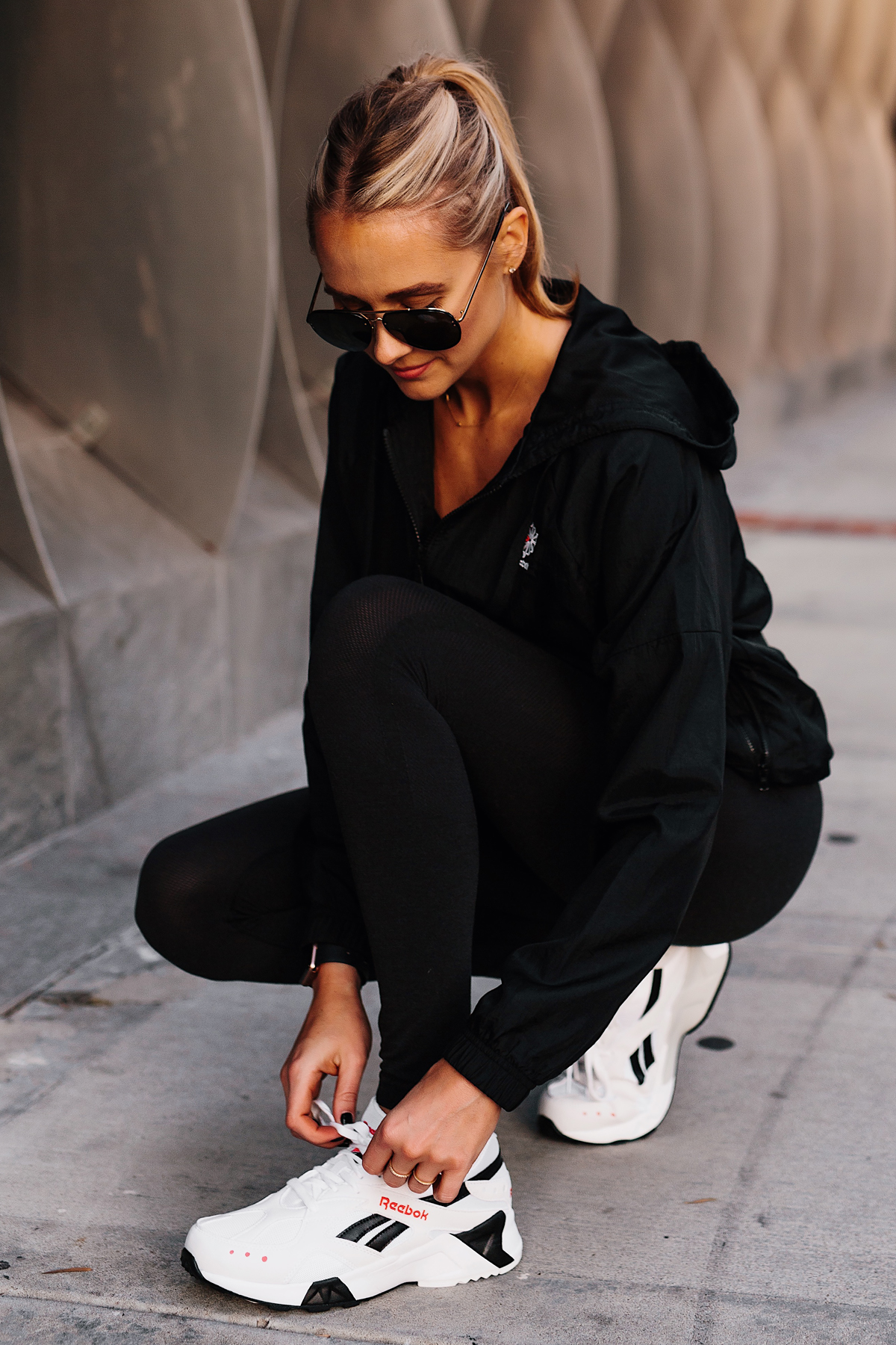 270fe089b912f Blonde Woman Wearing Reebok Black Windbreaker Reebok Black Leggings Reebok  Aztrek Sneakers White Fashion Jackson San