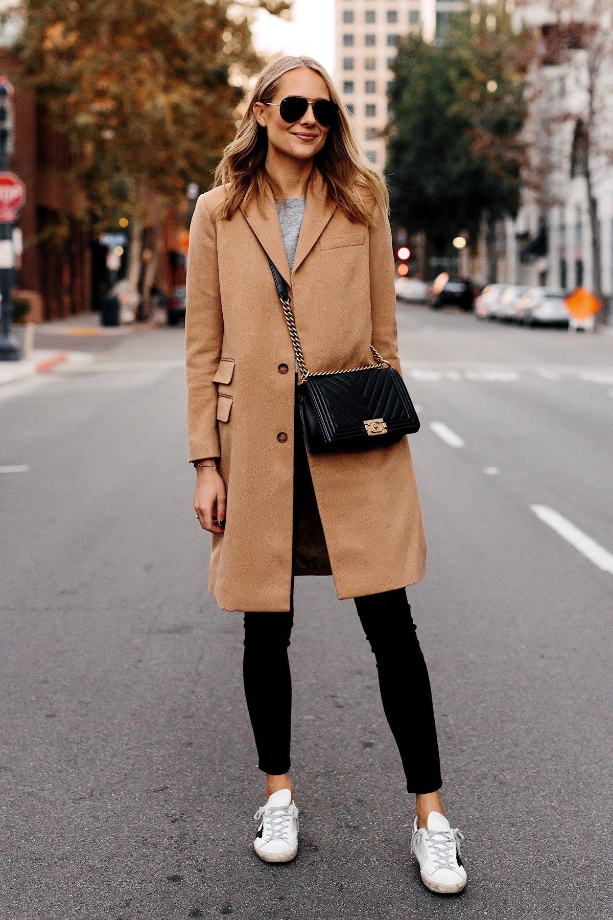 Blonde Woman Wearing Camel Coat Grey Sweater Black Skinny Jeans Golden Goose Sneakers Outfit Chanel Black Boy Bag Fashion Jackson San Diego Fashion Blogger Street Style