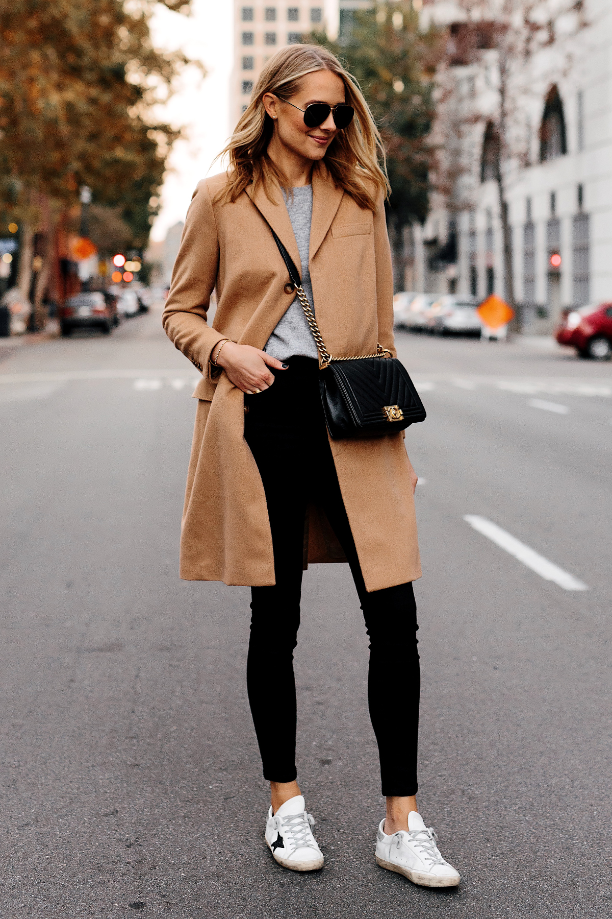 Blonde Woman Wearing Wearing Camel Coat Grey Sweater Black Skinny Jeans Golden Goose Sneakers Outfit Chanel Black Boy Bag Fashion Jackson San Diego Fashion Blogger Street Style