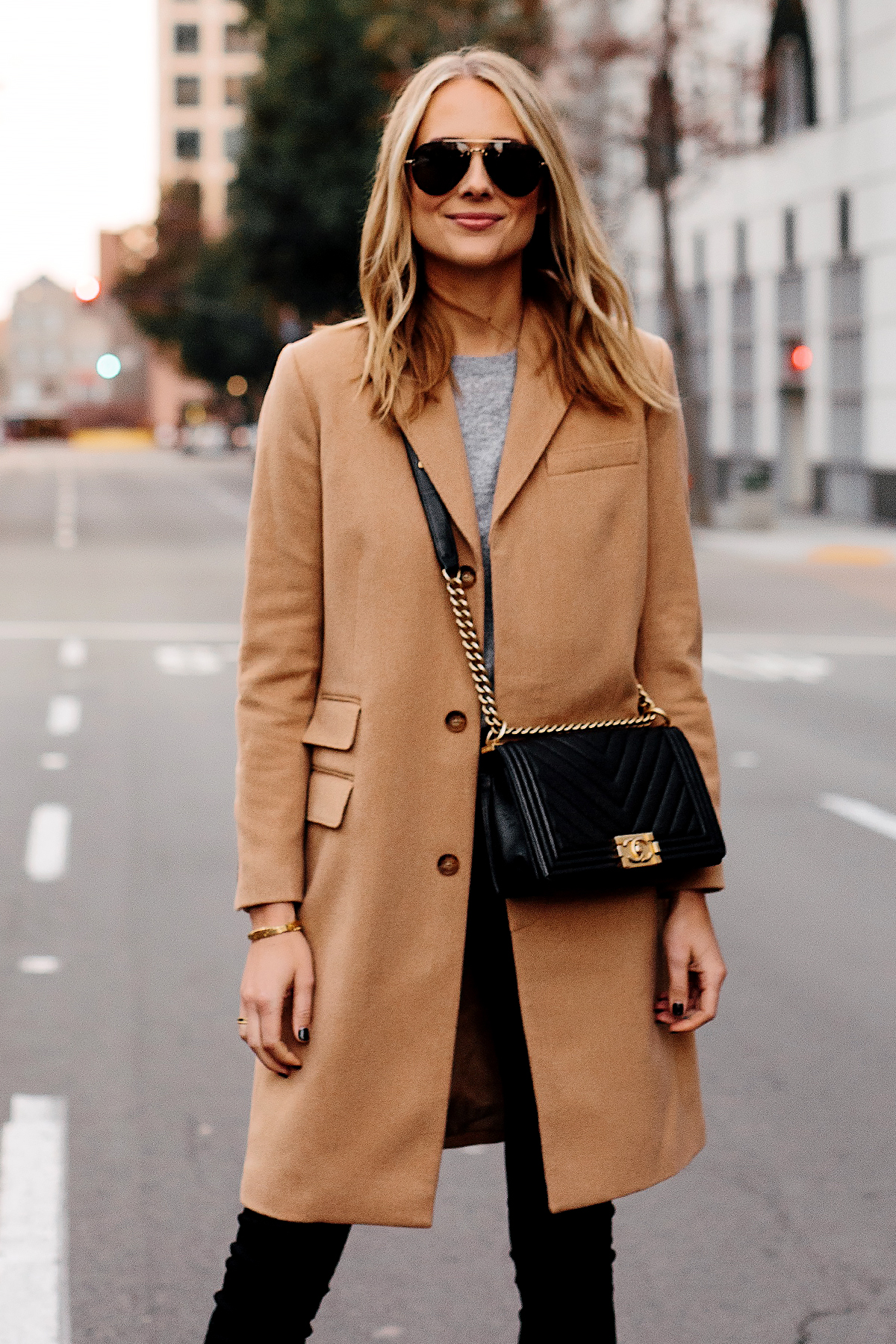 Blonde Woman Wearing Camel Coat Grey Sweater Black Skinny Jeans Outfit Chanel Black Boy Bag Fashion Jackson San Diego Fashion Blogger Street Style