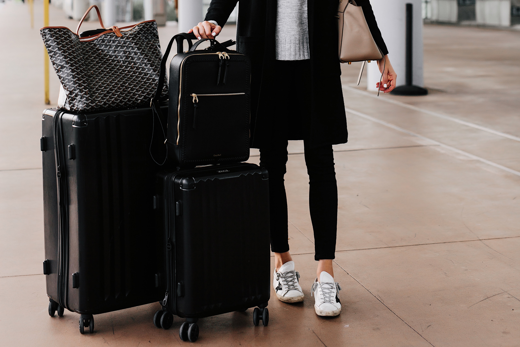 Woman at Airport with Calpak Kaya Black Backpack Calpak Black Luggage Goyard Tote Airport Style