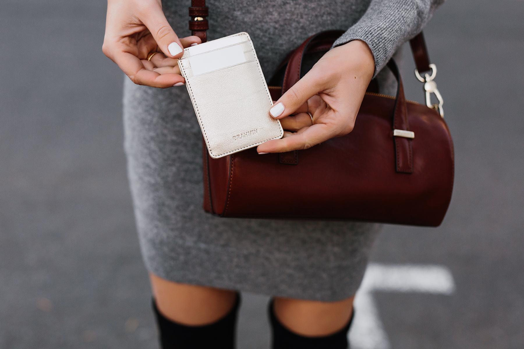 Woman Holding Brahmin Gold Card Case Brahmin Cognac Crossbody Grey Sweater Dress Fashion Jackson San Diego Fashion Blogger Street Style
