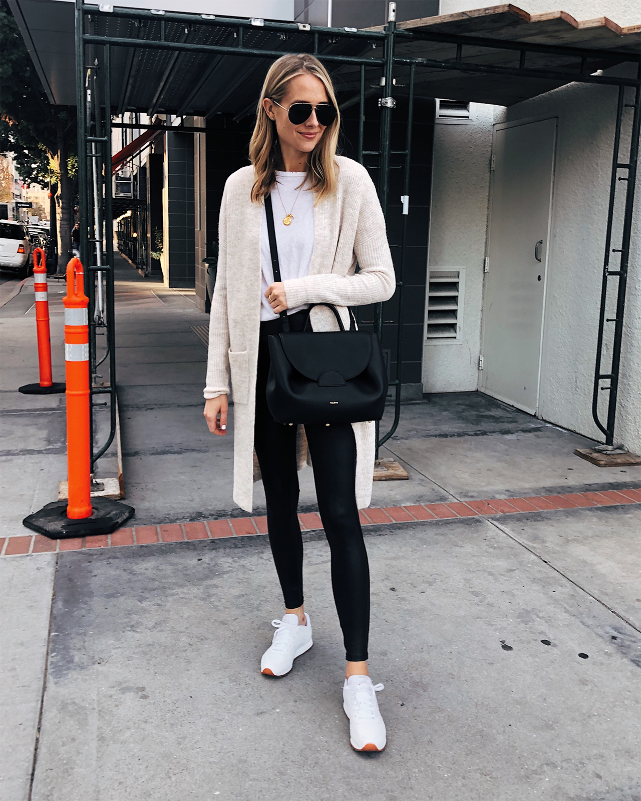 Fashion Jackson Wearing Beige Cardigan White Tshirt Black Leggings White Reebok Classic Sneakers Black Polene Handbag