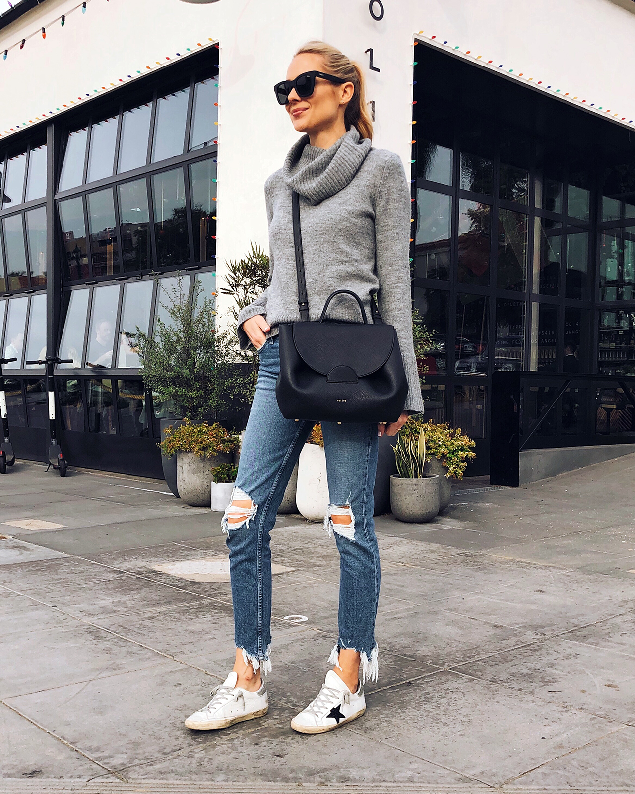 Fashion Jackson Wearing Ann Taylor Grey Turtleneck Sweater Paige Ripped Jeans Golden Goose Sneakers Polene Black Handbag