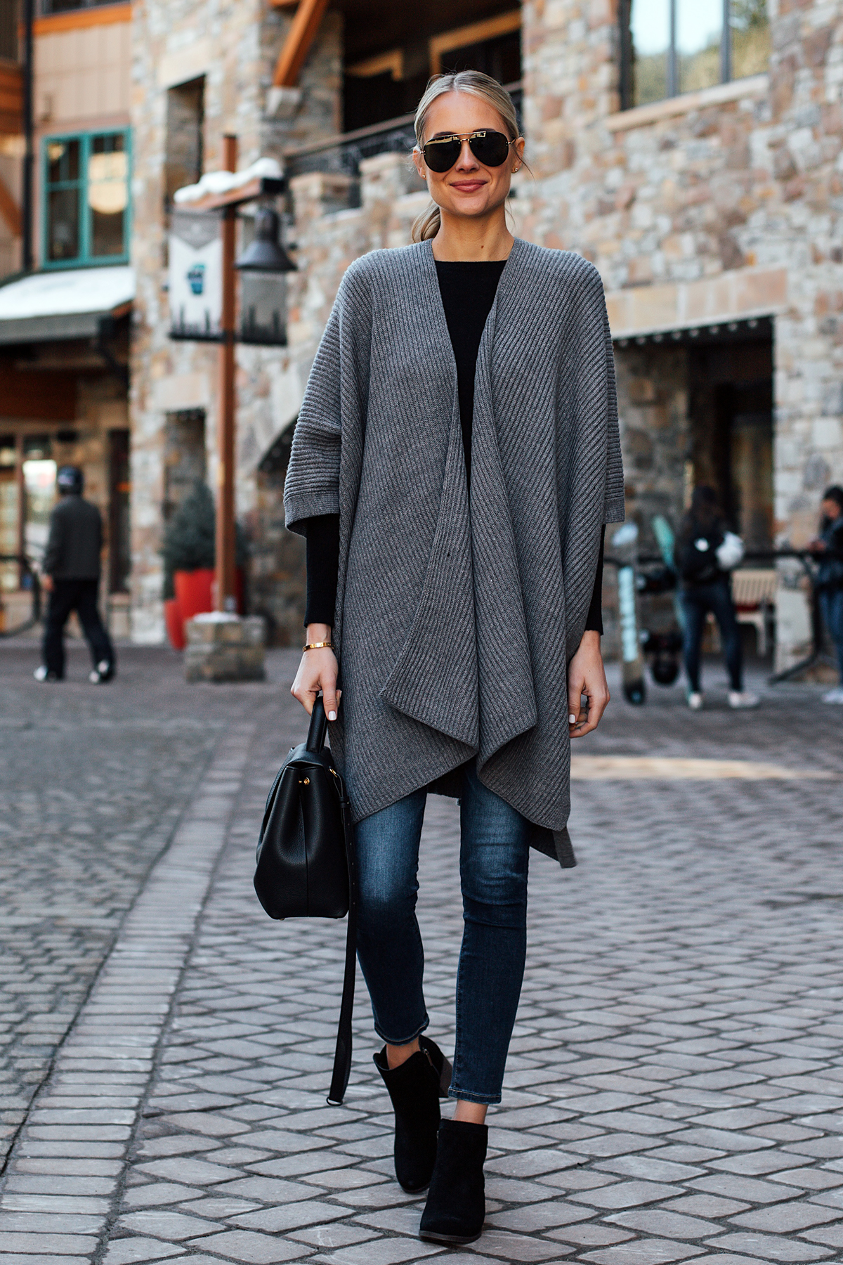 Blonde Woman Wearing All Saints Grey Sweater Poncho Denim Skinny Jeans Black Booties Polene Black Handbag Fashion Jackson San Diego Fashion Blogger Street Style