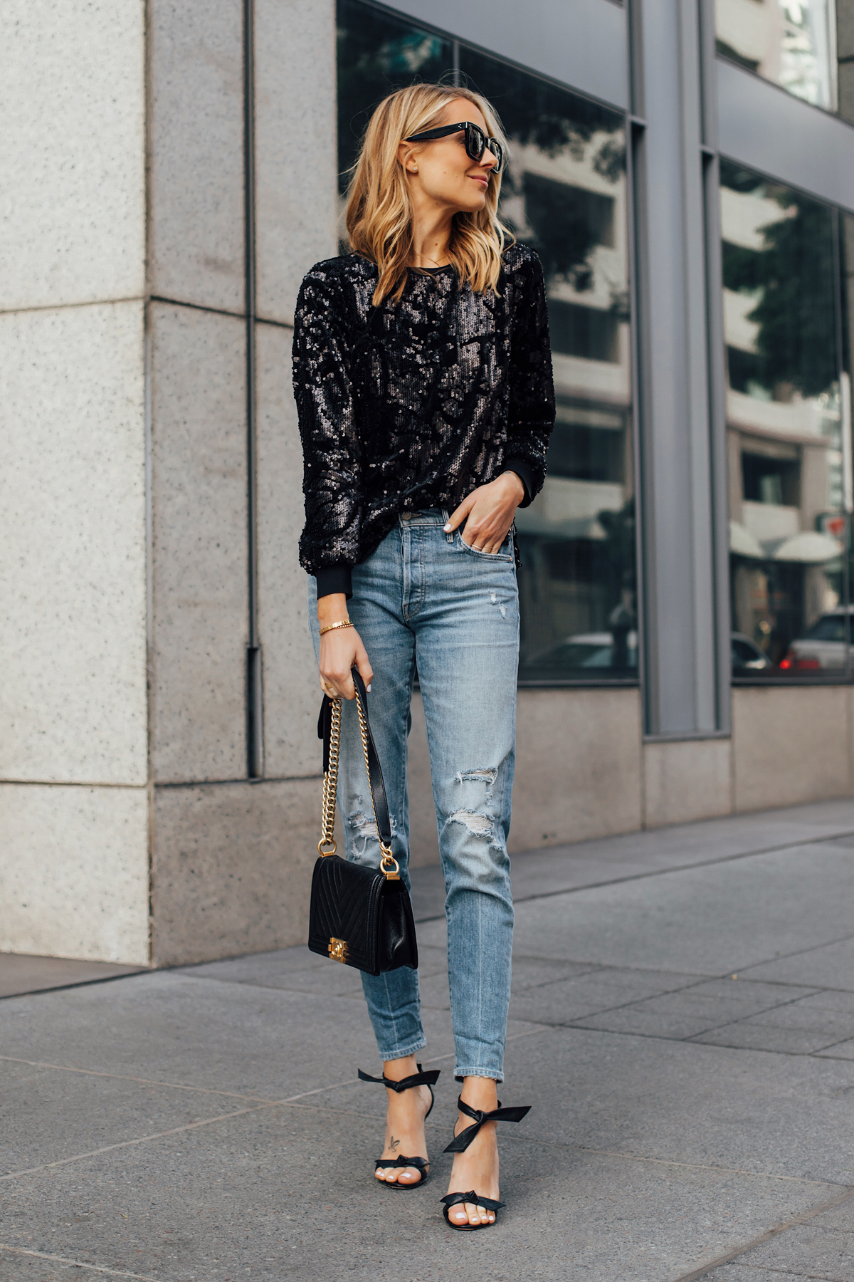 f4955970a9ca9 Blonde Woman Wearing Black Sequin Top Ripped Skinny Jeans Chanel Black Boy  Bag Black Ankle Tie
