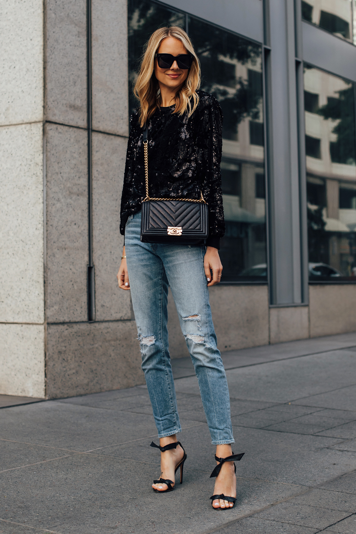 Blonde Woman Wearing Black Sequin Top Ripped Skinny Jeans Chanel Black Boy Bag Black Ankle Tie Heeled Sandals Fashion Jackson San Diego Fashion Blogger Street Style NYE Outfit
