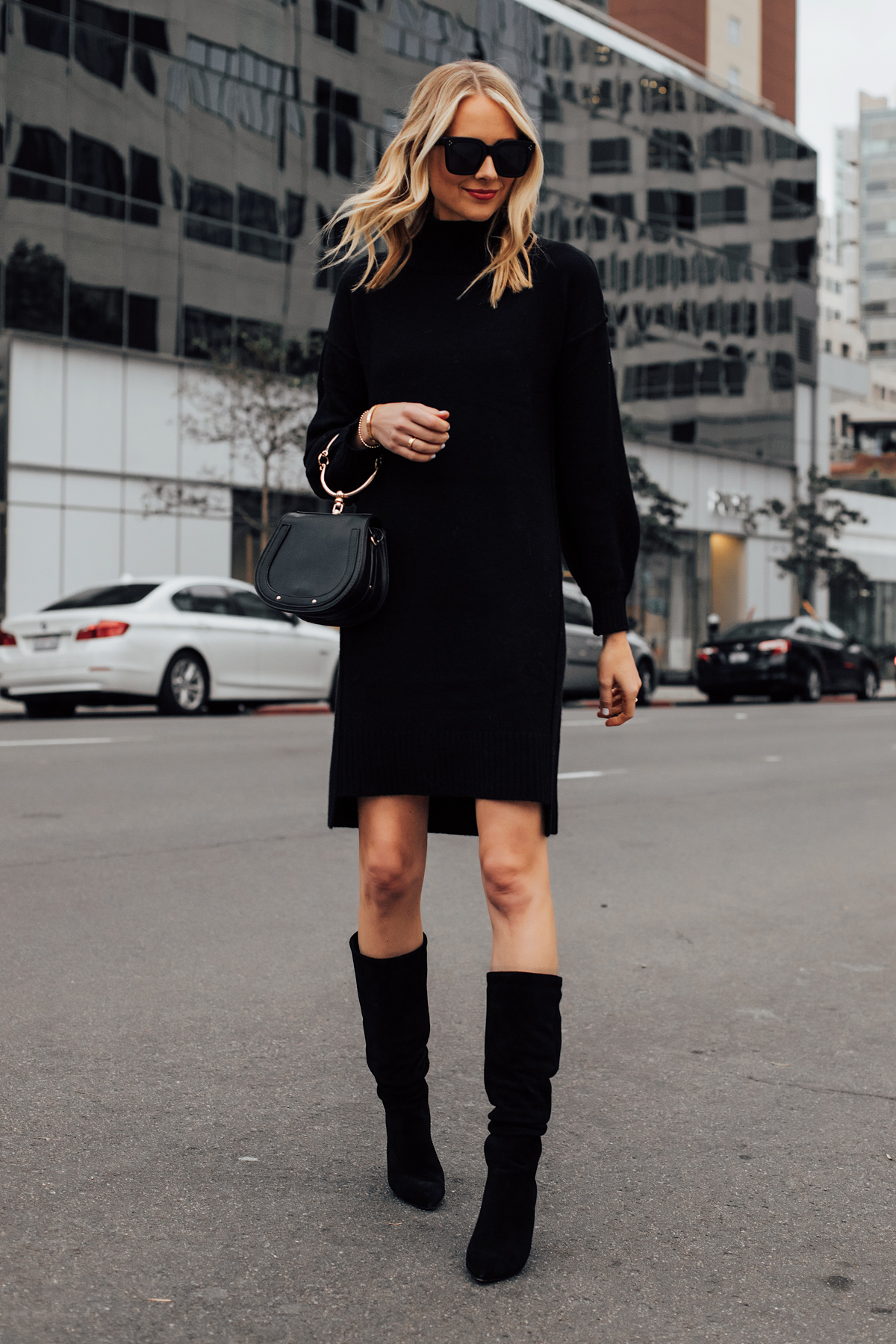 Blonde Woman Wearing Black Sweater Dress Black Tall Boots Black Clutch Handbag Fashion Jackson San Diego Fashion Blogger Street Style