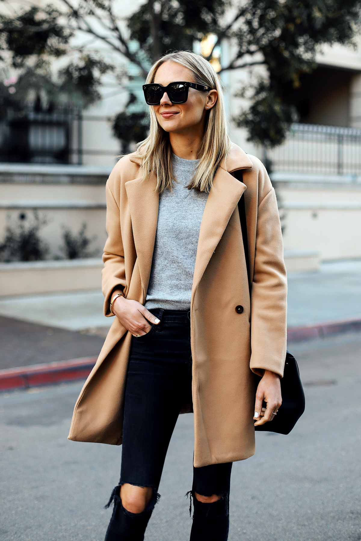 Blonde Woman Wearing Camel Coat Grey Sweater Black Ripped Skinny Jeans Outfit Fashion Jackson San Diego Fashion Blogger Street Style