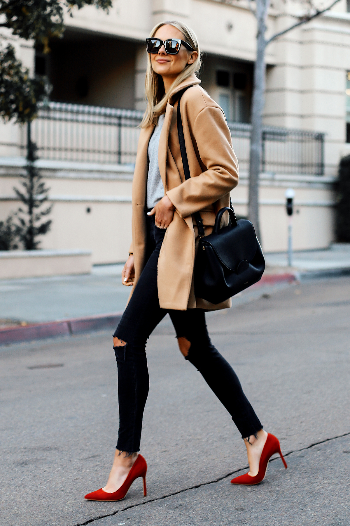 Blonde Woman Wearing Camel Coat Grey Sweater Black Ripped Skinny Jeans Red Pumps Outfit Black Satchel Handbag Fashion Jackson San Diego Fashion Blogger Street Style