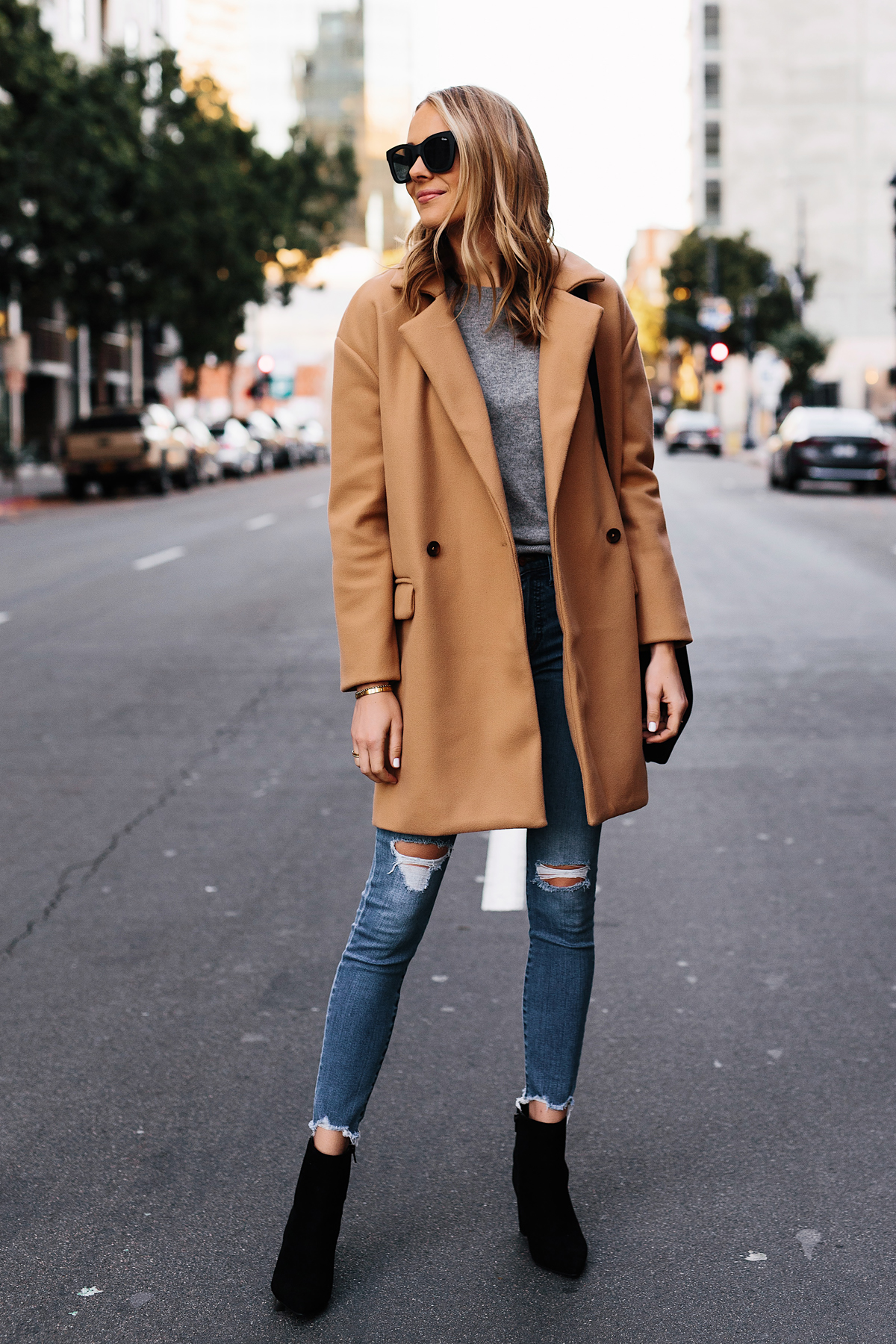 Blonde Woman Wearing Camel Coat Grey Sweater Denim Ripped Skinny Jeans Black Booties Outfit Fashion Jackson San Diego Fashion Blogger Street Style