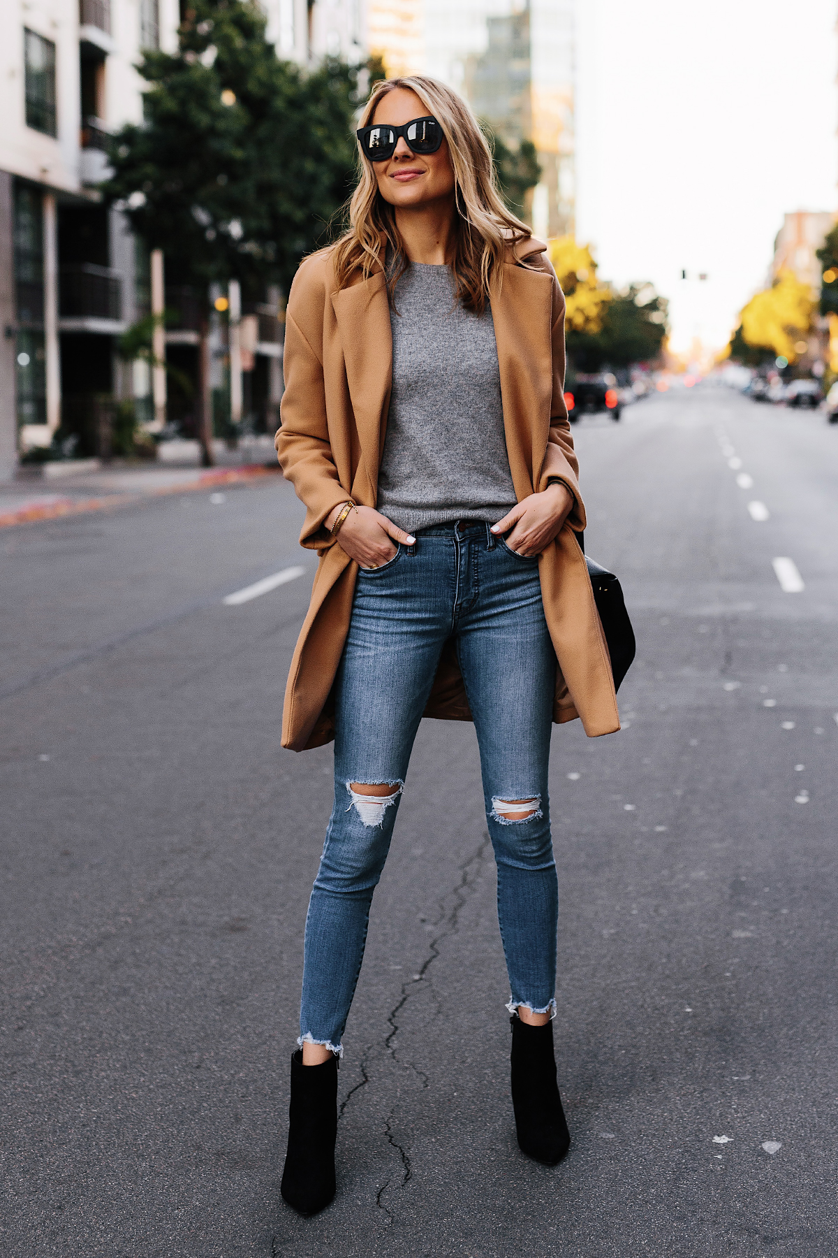 Blonde Woman Wearing Wearing Camel Coat Grey Sweater Denim Ripped Skinny Jeans Black Booties Outfit Fashion Jackson San Diego Fashion Blogger Street Style