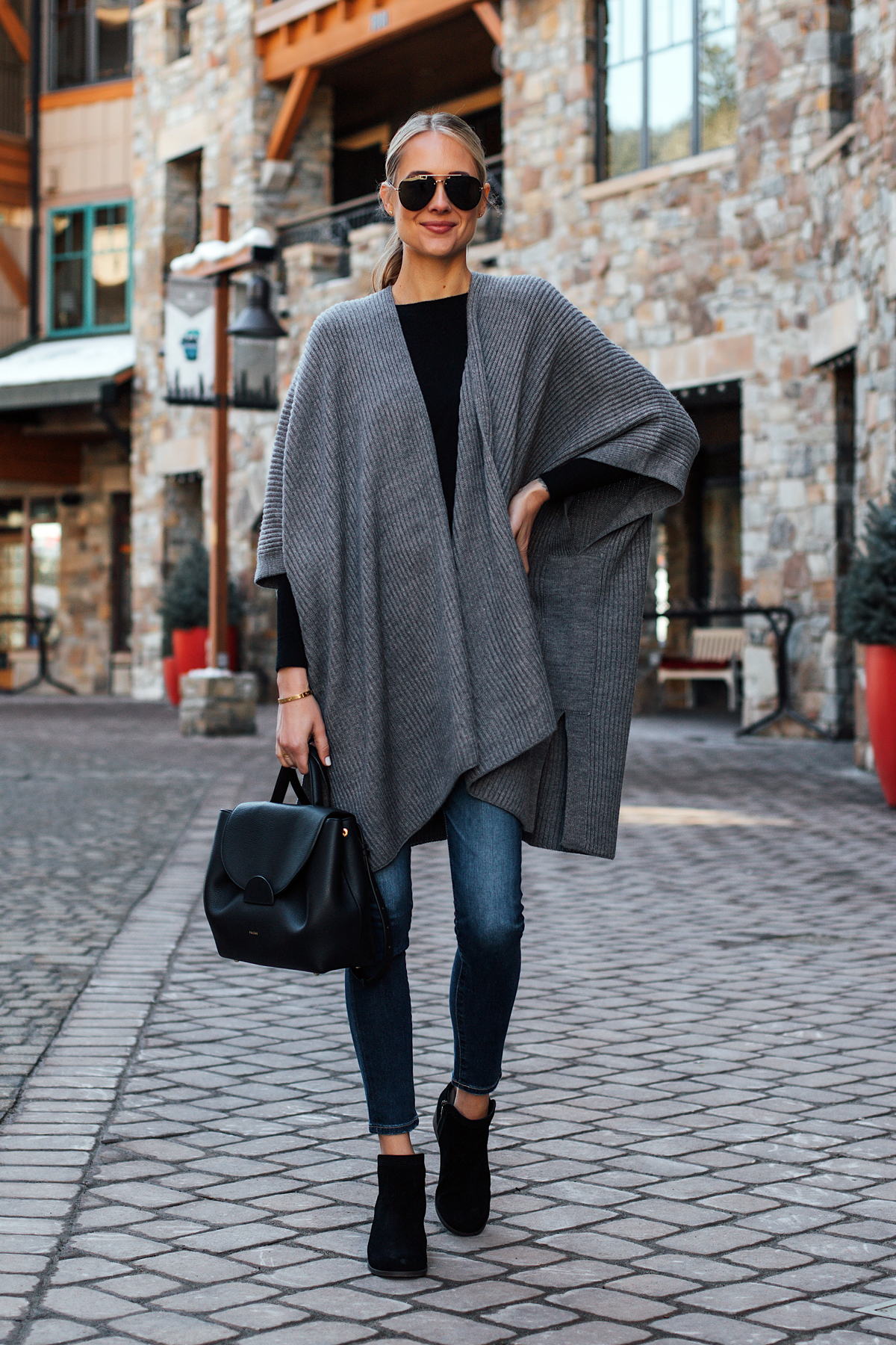 Blonde Woman Wearing Grey Sweater Poncho Black Top Denim Skinny Jeans Koolaburra Black Booties Polene Black Handbag Fashion Jackson San Diego Fashion Blogger Street Style