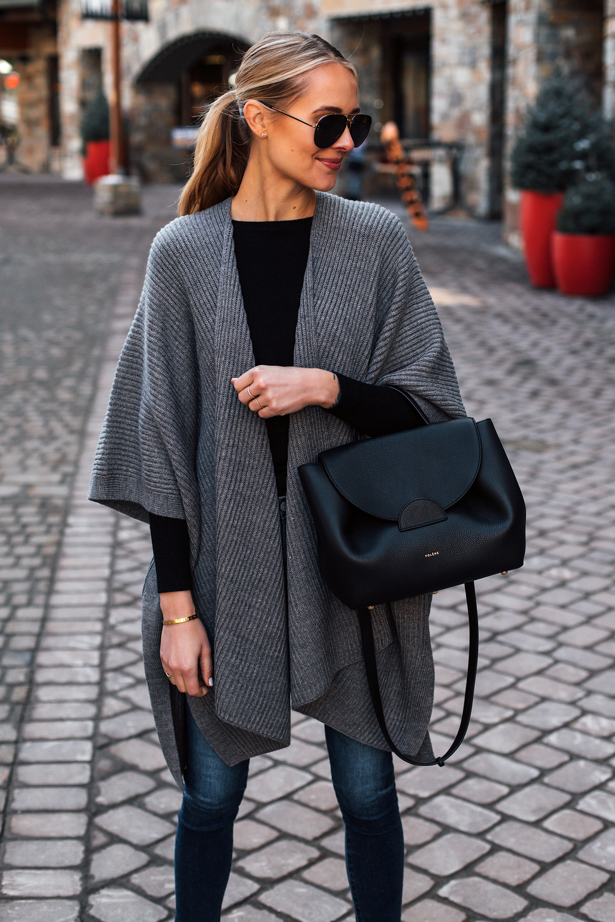 Blonde Woman Wearing Grey Sweater Poncho Black Top Denim Skinny Jeans Polene Black Handbag Outfit Fashion Jackson San Diego Fashion Blogger Street Style
