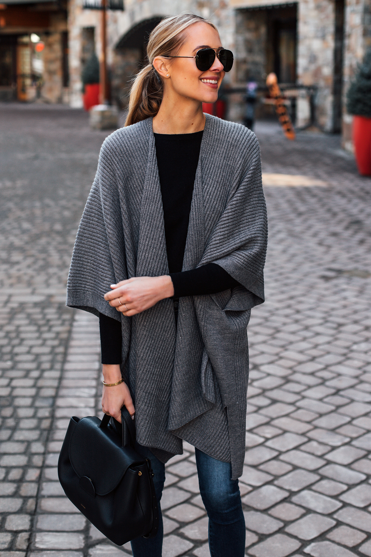 Blonde Woman Wearing Grey Sweater Poncho Black Top Denim Skinny Jeans Polene Black Handbag Fashion Jackson San Diego Fashion Blogger Street Style
