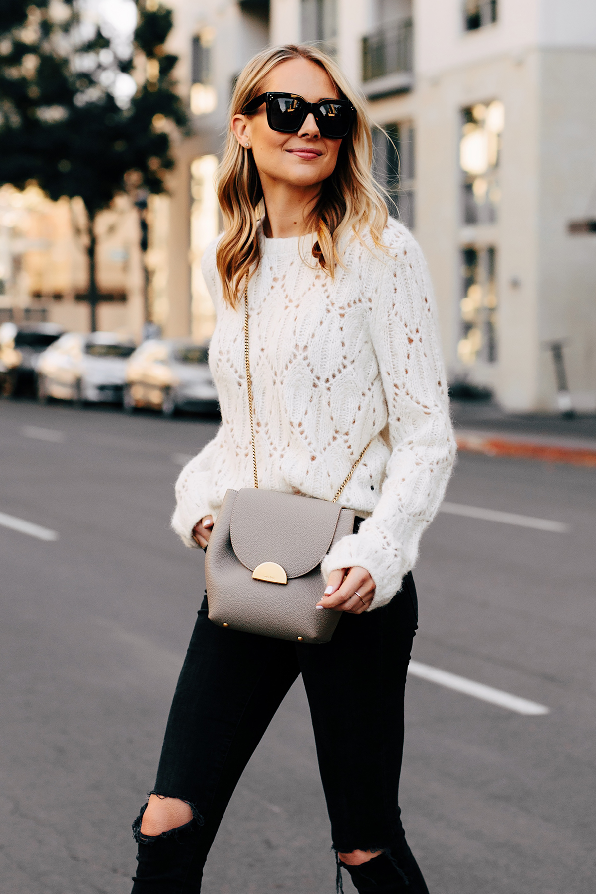 Blonde Woman Wearing Reformation White Pointelle Sweater Madewell Black Ripped Skinny Jeans Polene Grey Handbag Fashion Jackson San Diego Fashion Blogger Street Style