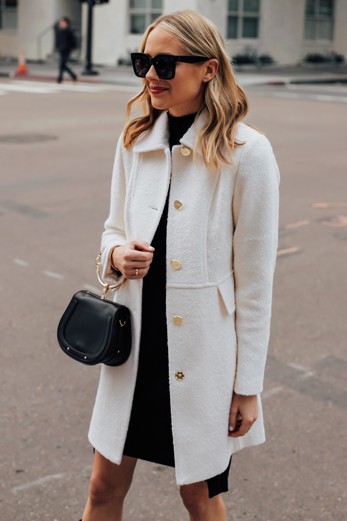 Blonde Woman Wearing Winter White Coat Black Sweater Dress Black Clutch Handbag Fashion Jackson San Diego Fashion Blogger Holiday Style