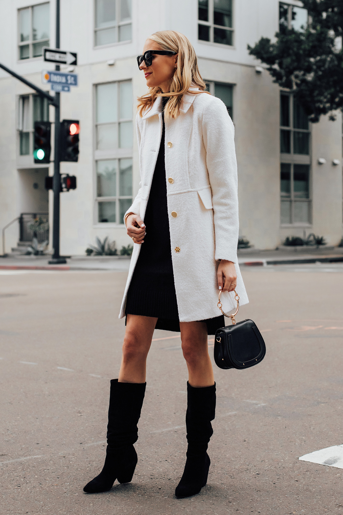 Blonde Woman Wearing Winter White Coat Black Sweater Dress Black Slouchy Boots Black Clutch Handbag Fashion Jackson San Diego Fashion Blogger Holiday Style