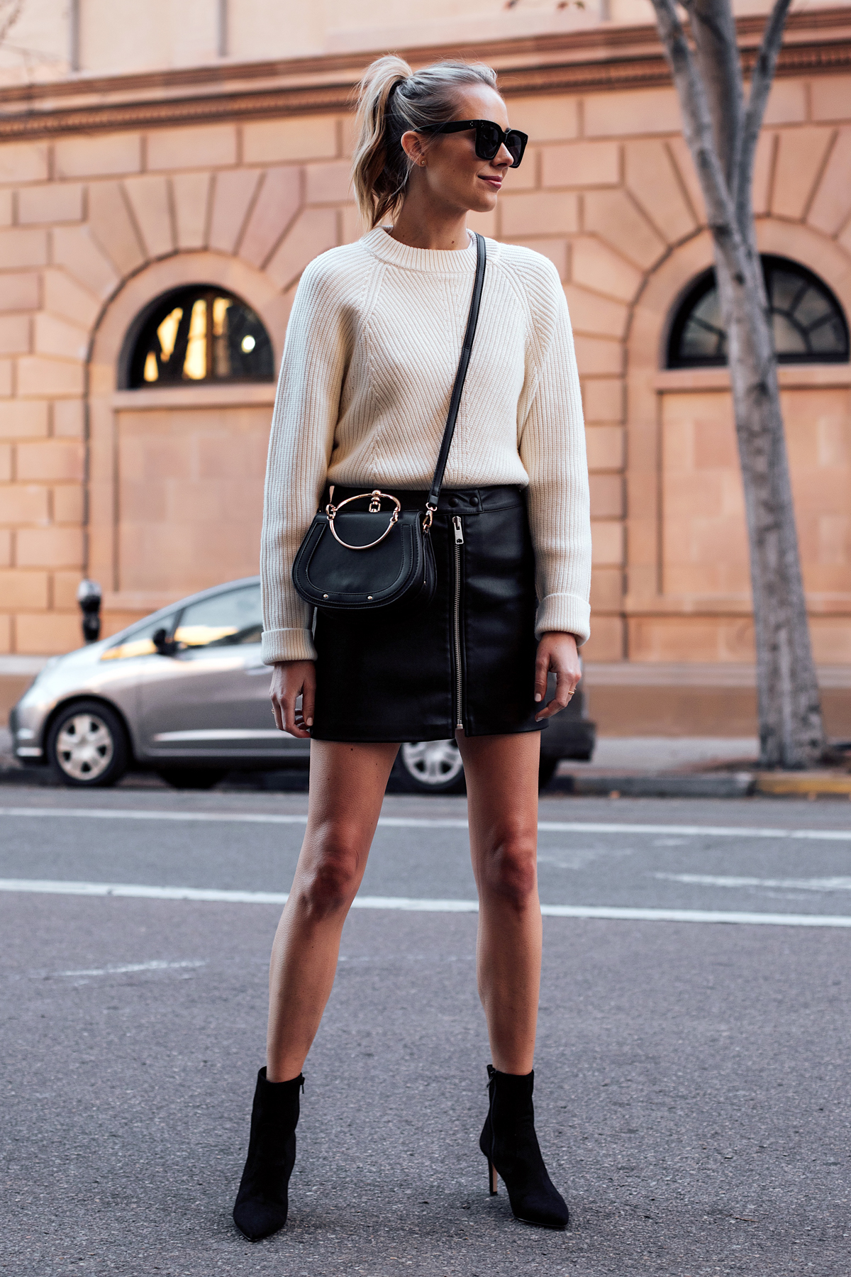 Blonde Woman Wearing AllSaints White Sweater Black Faux Leather Mini Skirt Black Chloe Nile Dupe Black Ankle Booties Fashion Jackson San Diego Fashion Blogger Street Style