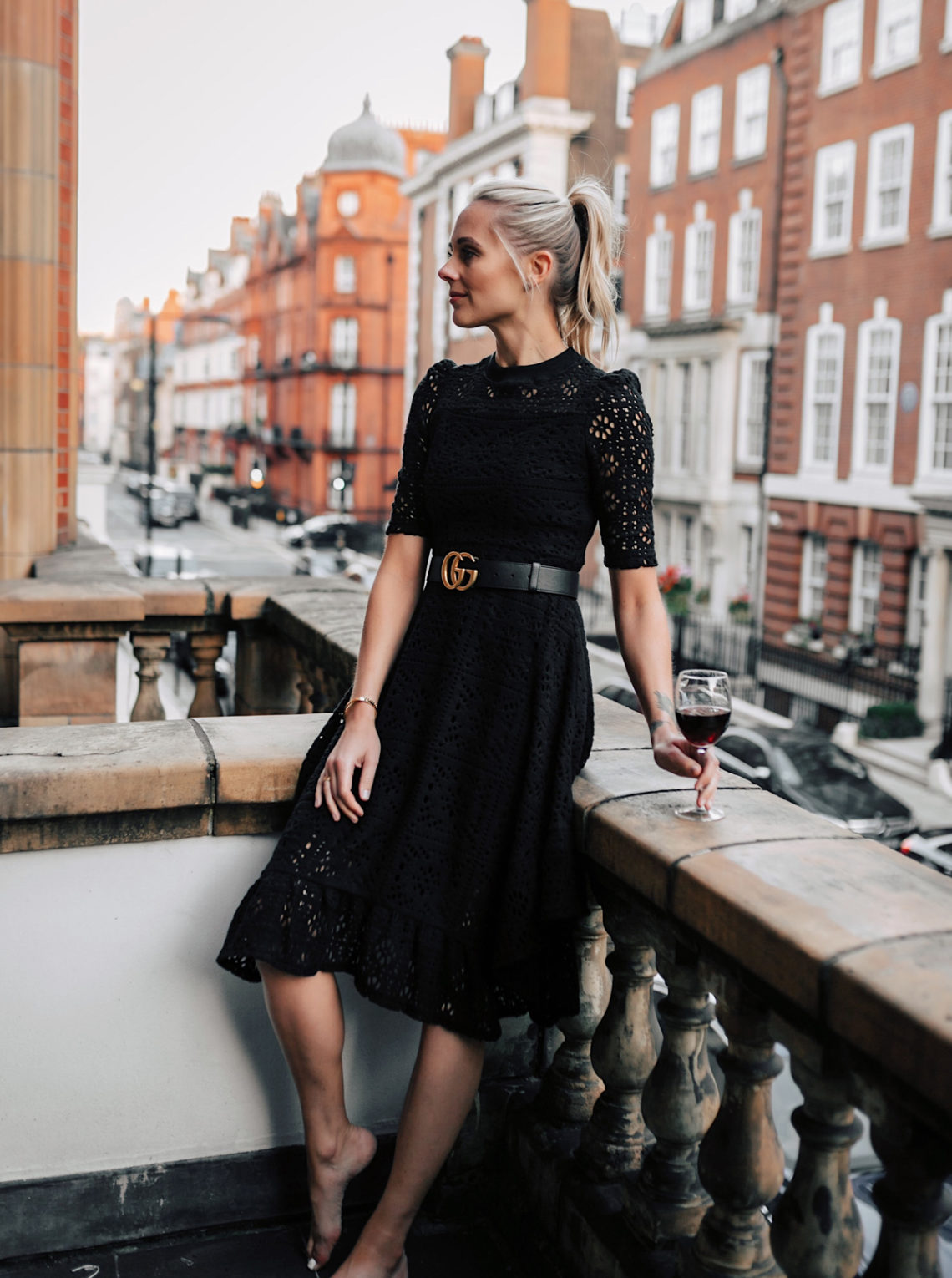 Blonde Women Wearing Black Lace Dress with Gucci Belt on London Balcony