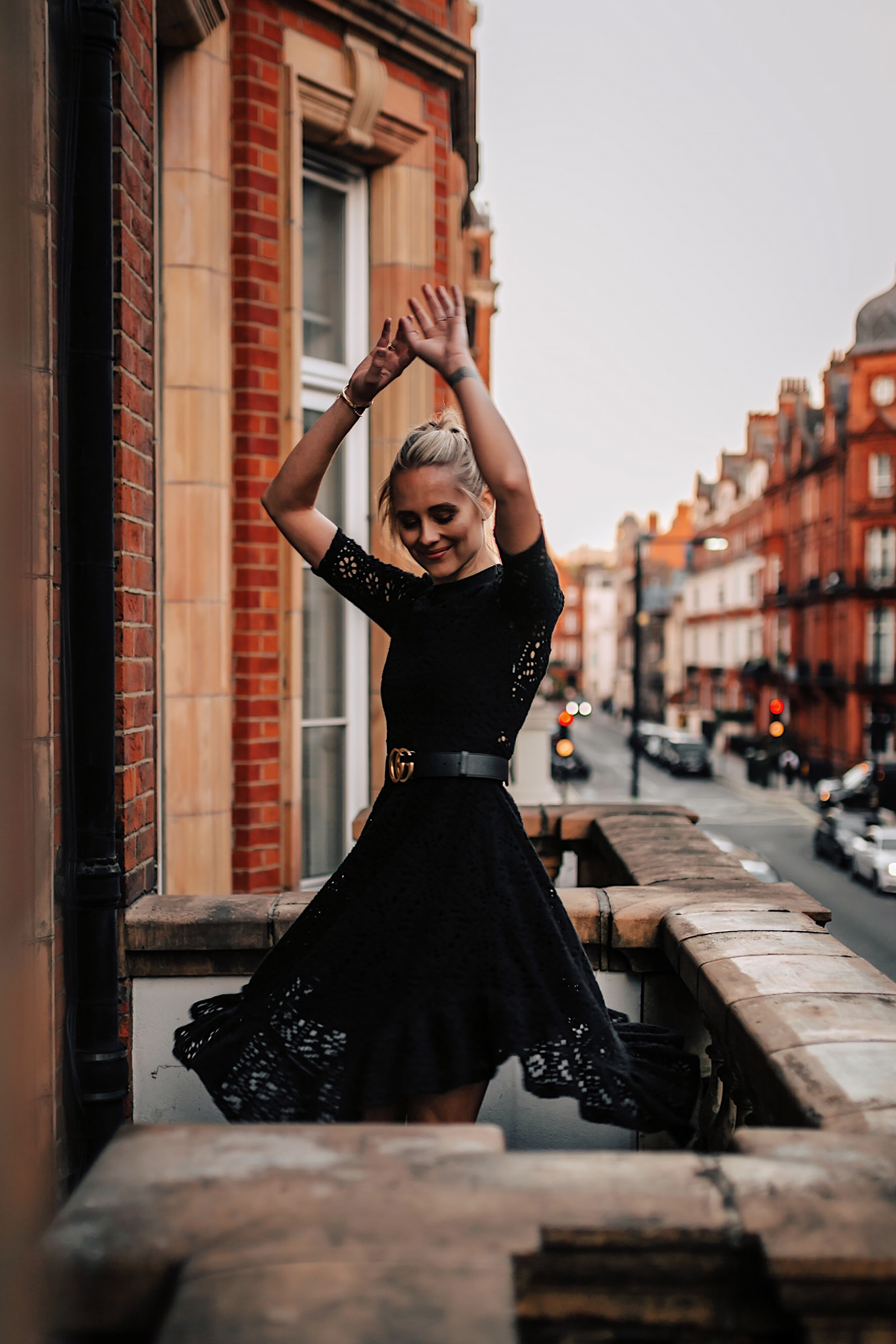 Blonde Women Twirling Wearing Black Lace Dress with Gucci Belt on London Balcony