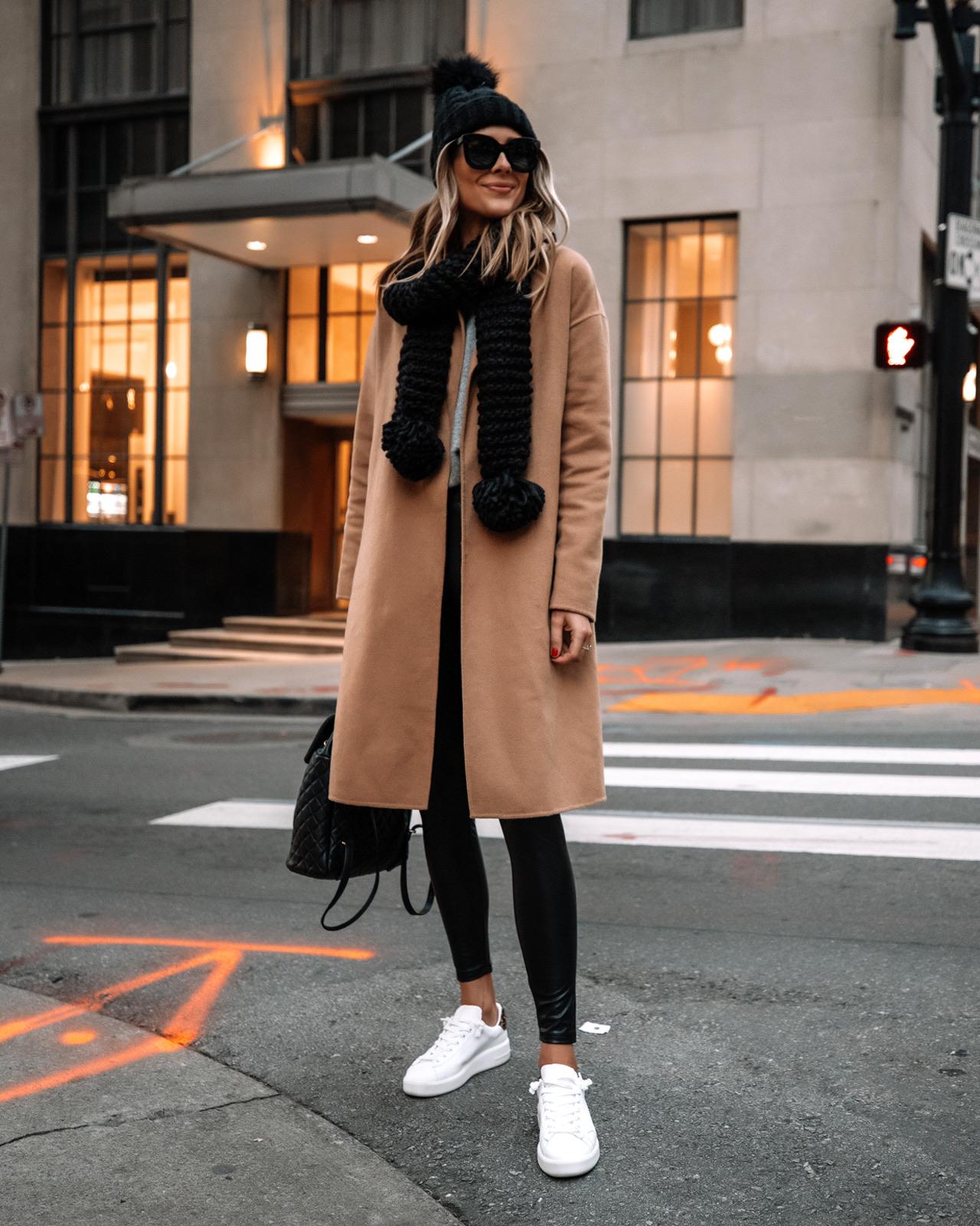Fashion Jackson Wearing Camel Coat Black Faux Leather Leggings White Sneakers Black Scarf Black Beanie Winter Outfit