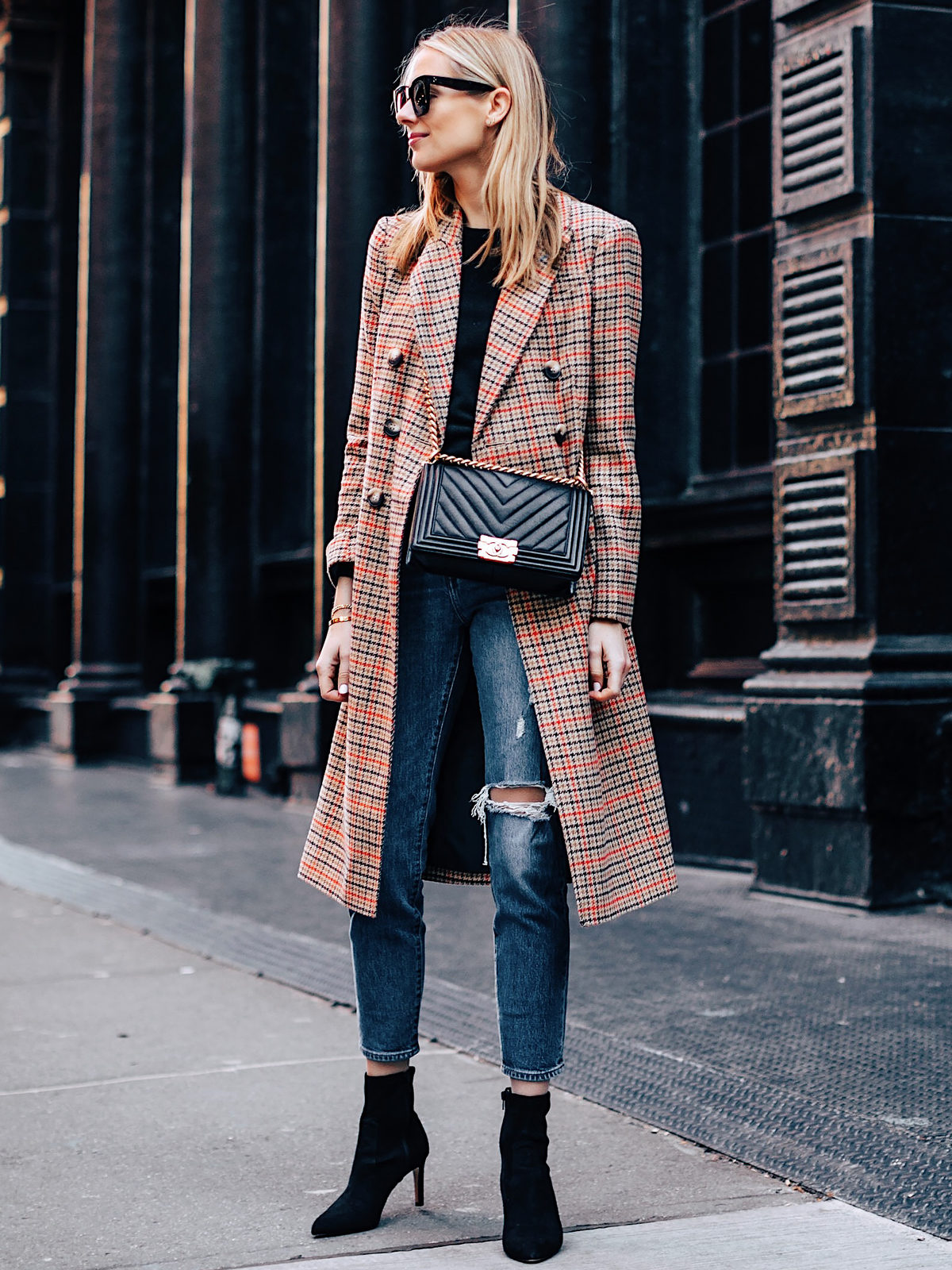 Blonde Woman Wearing Topshop Plaid Long Coat Black Sweater Levis Wedgie Fit Ripped Jeans Black Booties Chanel Boy Bag Black Fashion Jackson Fashion Blogger NYFW Street Style