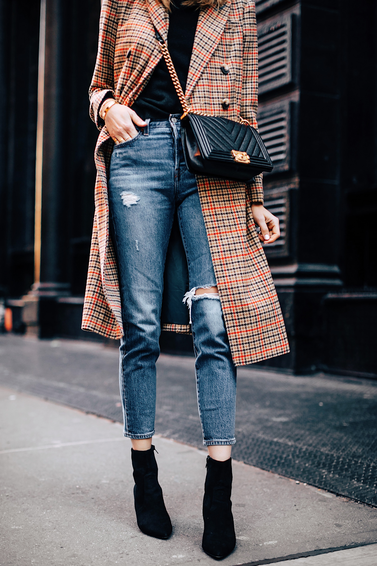 Woman Wearing Topshop Plaid Long Coat Black Sweater Levis Wedgie Fit Ripped Jeans Black Booties Chanel Boy Bag Black Fashion Jackson Fashion Blogger NYFW Street Style