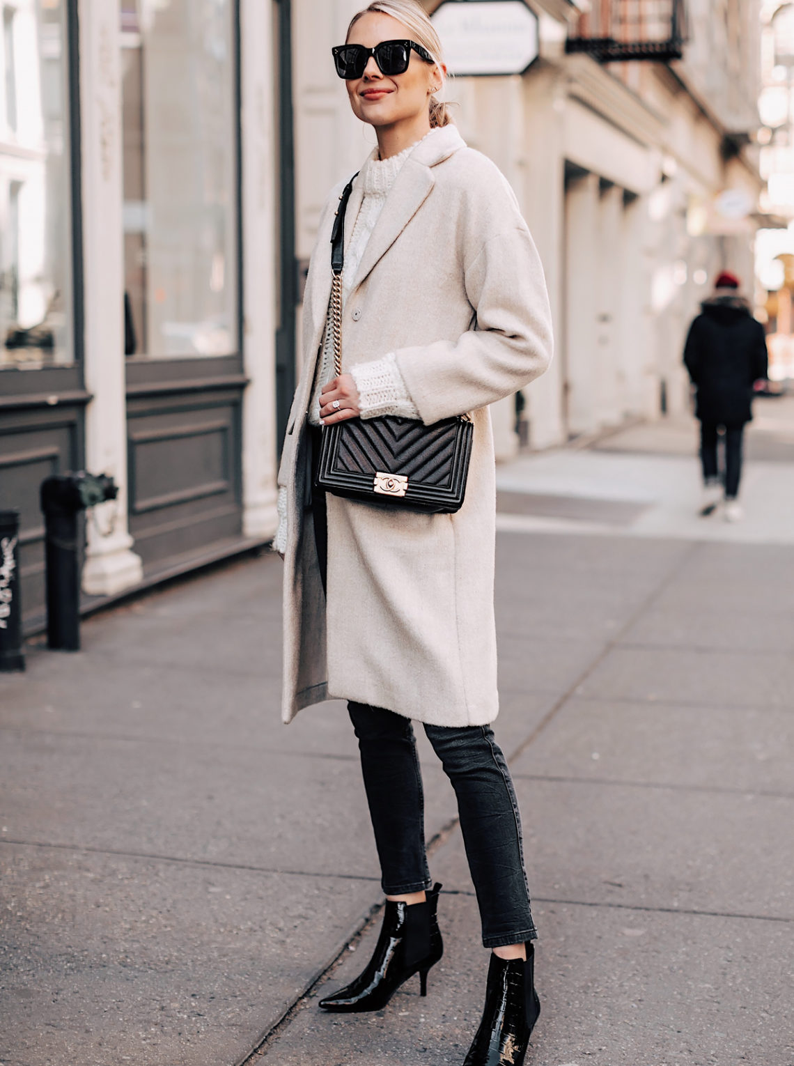 Blonde Woman Wearing White Knit Sweater Beige Coat Grey Skinny Jeans Black Ankle Booties Chanel Black Boy Bag Fashion Jackson Fashion Blogger NYFW Street Style
