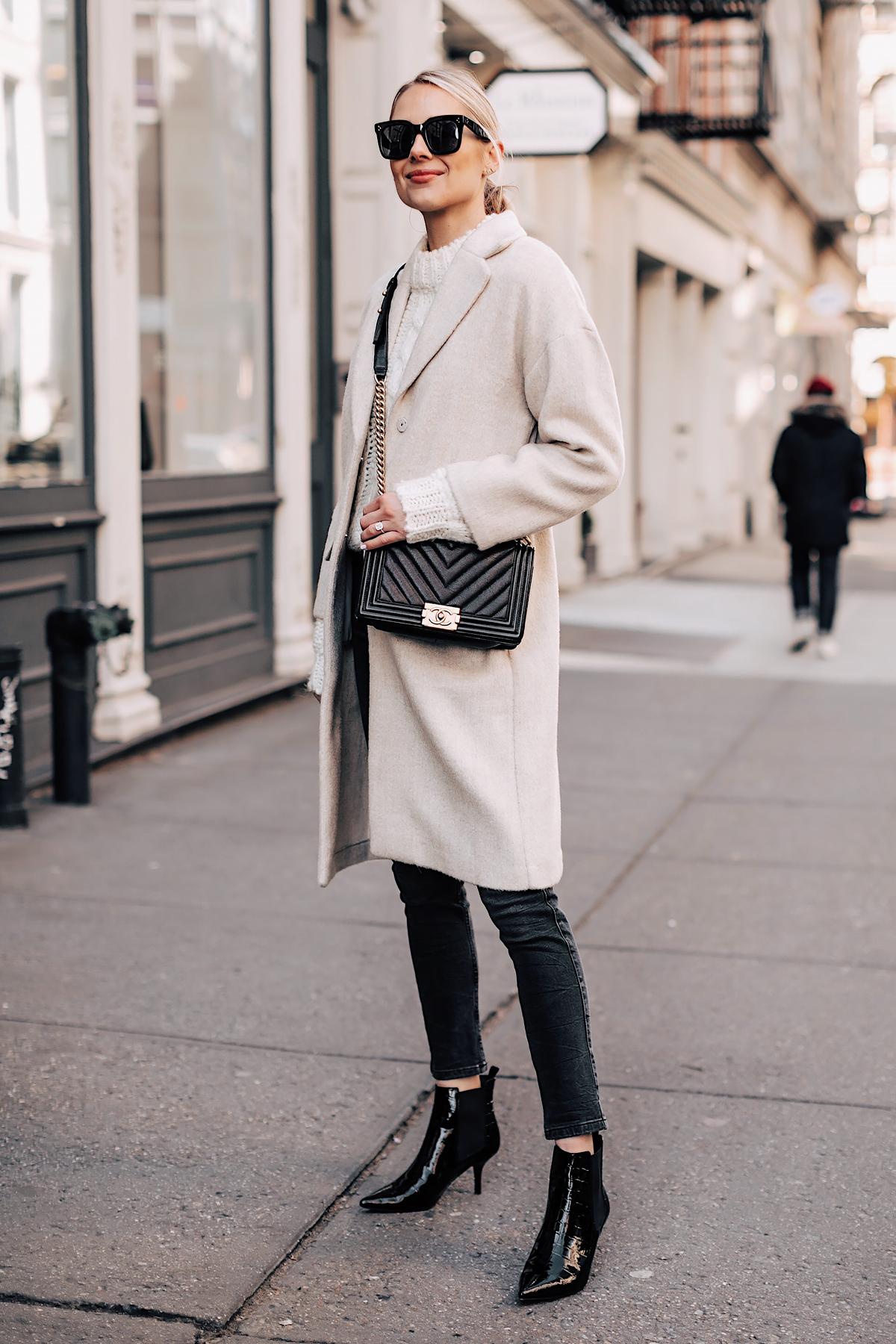 Blonde Woman Wearing White Knit Sweater Beige Coat Grey Skinny Jeans Black Ankle Booties Chanel Black Boy Bag Fashion Jackson Fashion Blogger NYFW Street Style