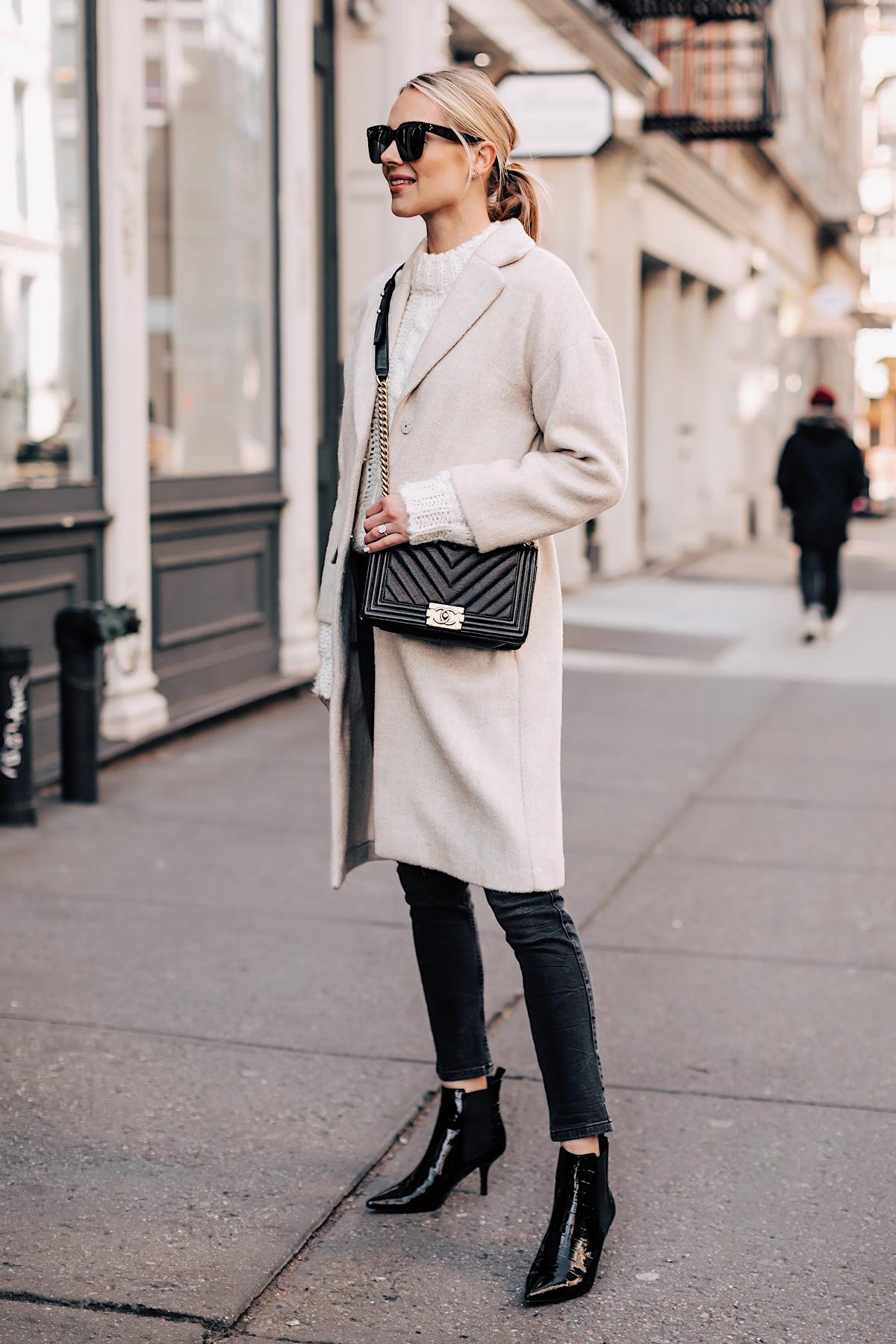 Blonde Woman Wearing White Knit Sweater Grey Skinny Jeans Beige Wool Coat Black Ankle Booties Chanel