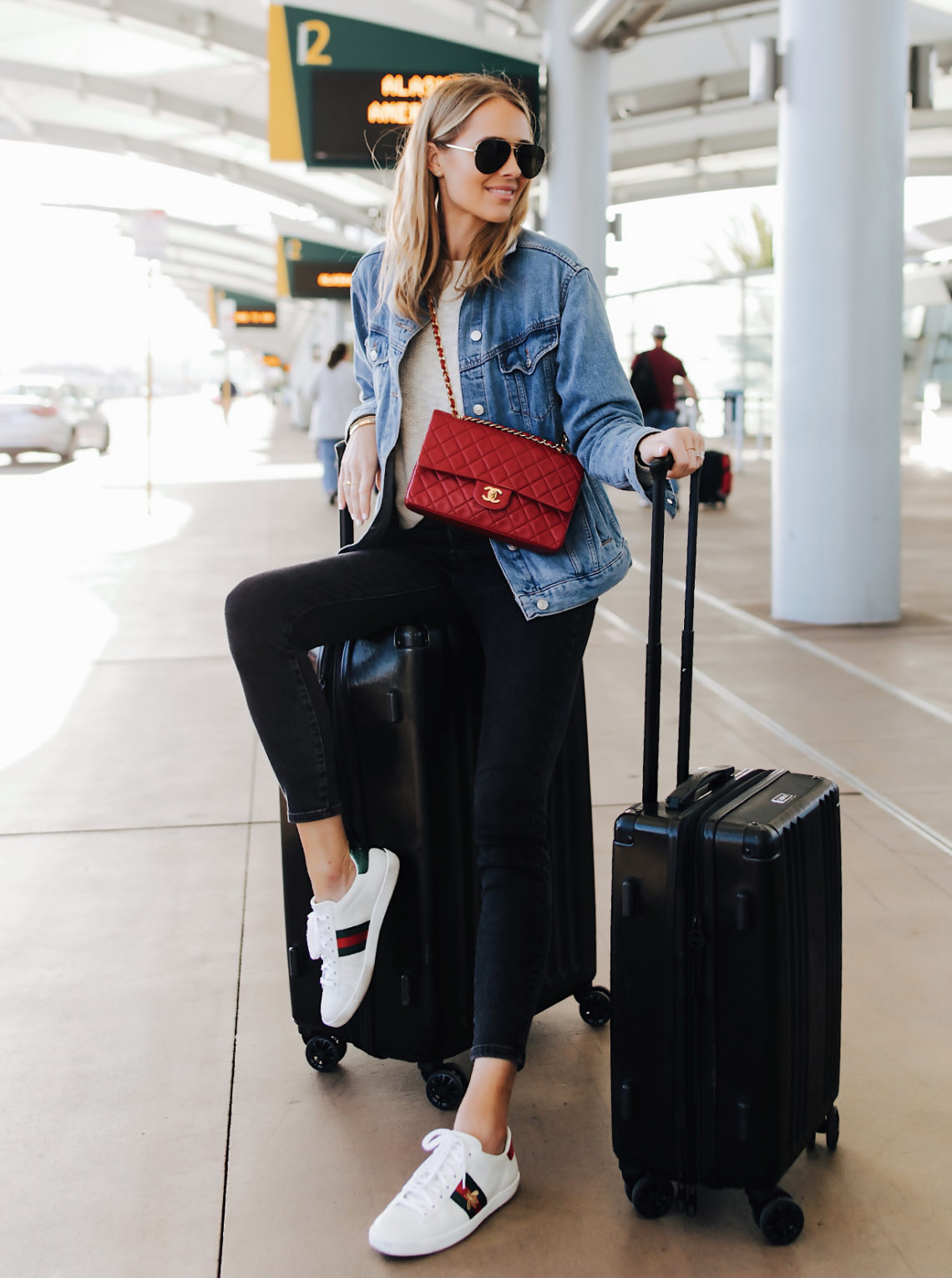 Fashion Jackson Airport Style Wearing Denim Jacket Black Skinny Jeans Gucci Sneakers Red Chanel Handbag Calpak Black Ambeur Spinner Luggage Set Featured Image