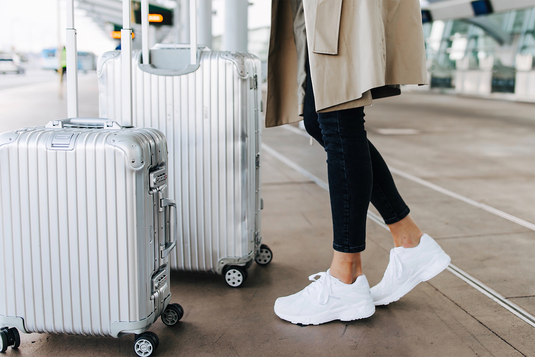 Woman Wearing Airport Travel Outfit Black Skinny Jeans Reebok Aztrek White Sneakers Rimowa Luggage Fashion Jackson San Diego Fashion Blogger Street Style