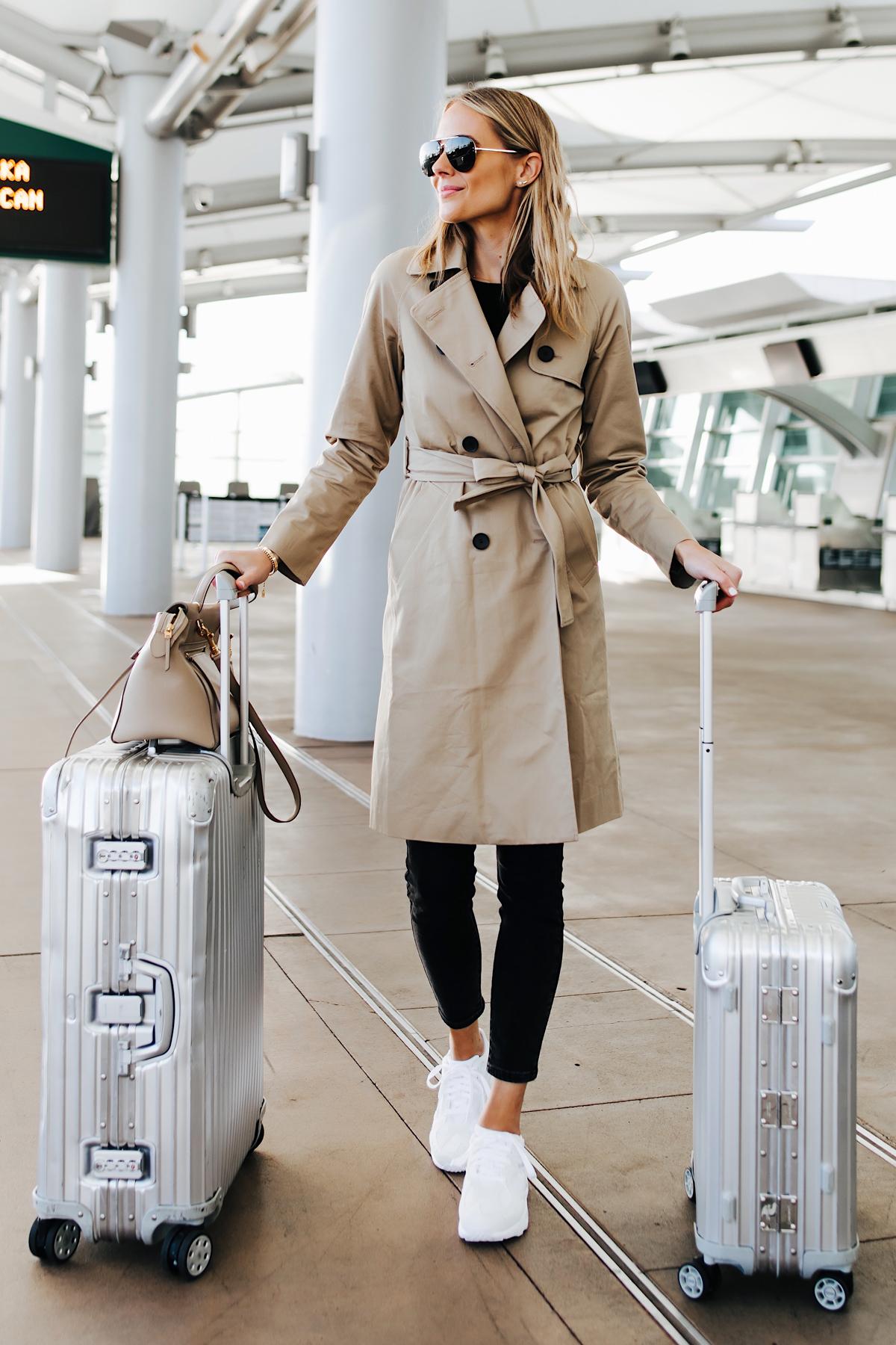 Blonde Woman Wearing Airport Travel Outfit Trench Coat Black Skinny Jeans Reebok Aztrek White Sneakers Rimowa Luggage Fashion Jackson San Diego Fashion Blogger Street Style